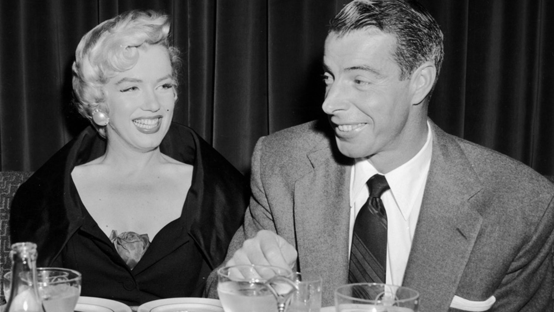 A portrait of Marilyn Monroe sitting with her husband Joe DiMaggio at El Morocco in New York City.