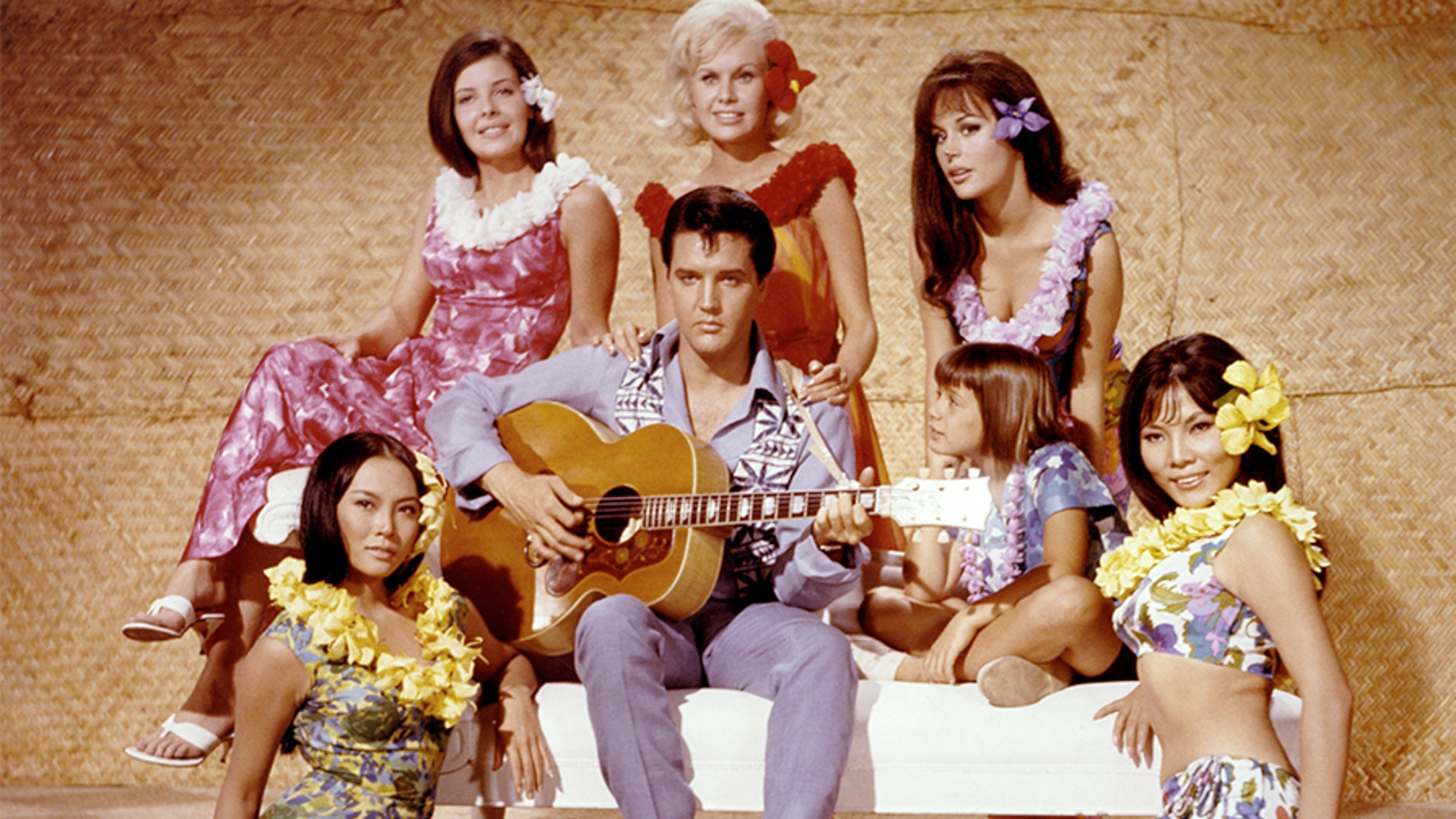 "Elvis Presley and other cast members appear on the set of the 1966 film ""Paradise, Hawaiian Style."" (Getty Images)"