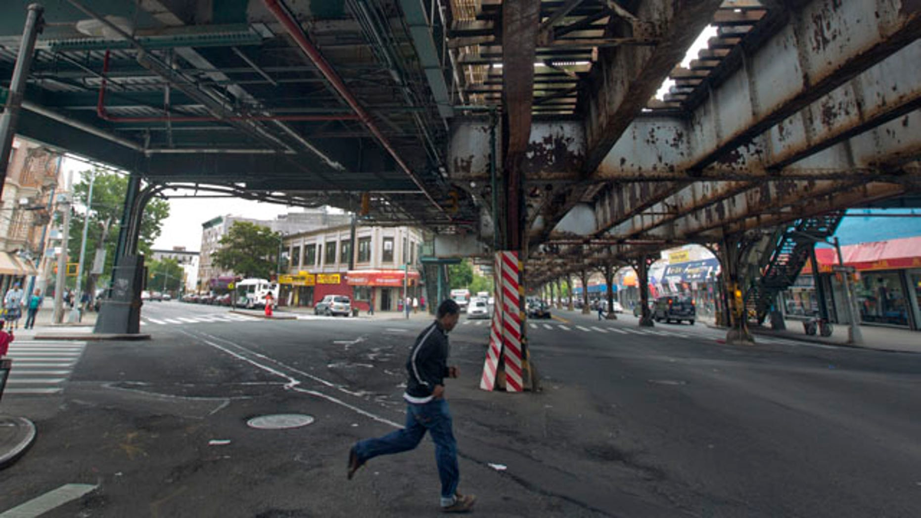 May 22, 2013: A young man runs under an elevated section of subway tracks in The Bronx borough of New York.