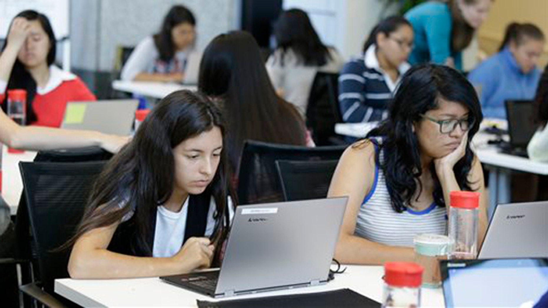 In this photo taken Wednesday, June 18, 2014, Bryanna Gilges, 15, left, and Yvonne Gonzalez, 17, right, work at completing an exercise during a Girls Who Code class at Adobe Systems in San Jose, Calif. Google is partnering with Girls Who Code, a national non-profit organization that aims to inspire, educate and equip young women for futures in the computing-related fields. (AP Photo/Eric Risberg)