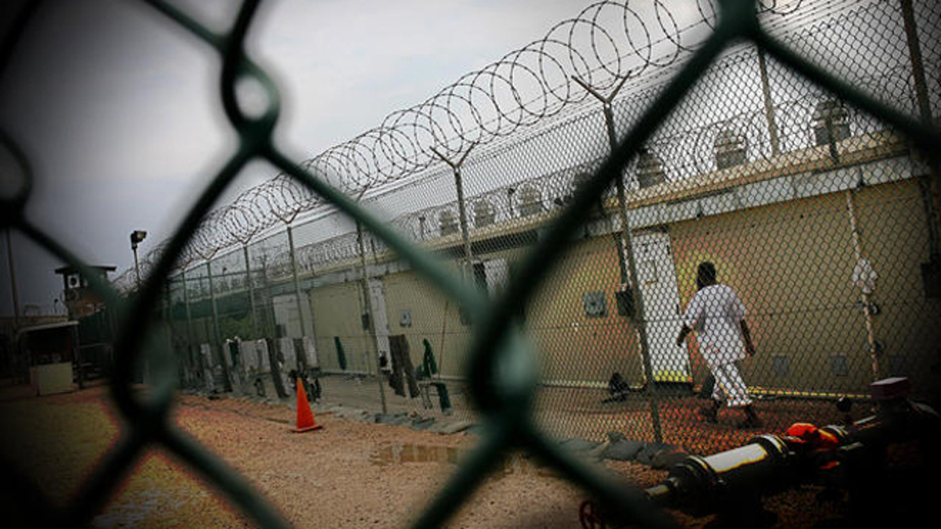 A detainee walks in Camp 4 at the Guantanamo Bay US Naval Base in Cuba Wednesday, May 14, 2008. Camp 4 is a medium security facility for cooperative prisoners who get to wear white uniforms and are allowed to share a cell with up to 9 other detainees. (AP Photo/Rodrigo Abd)