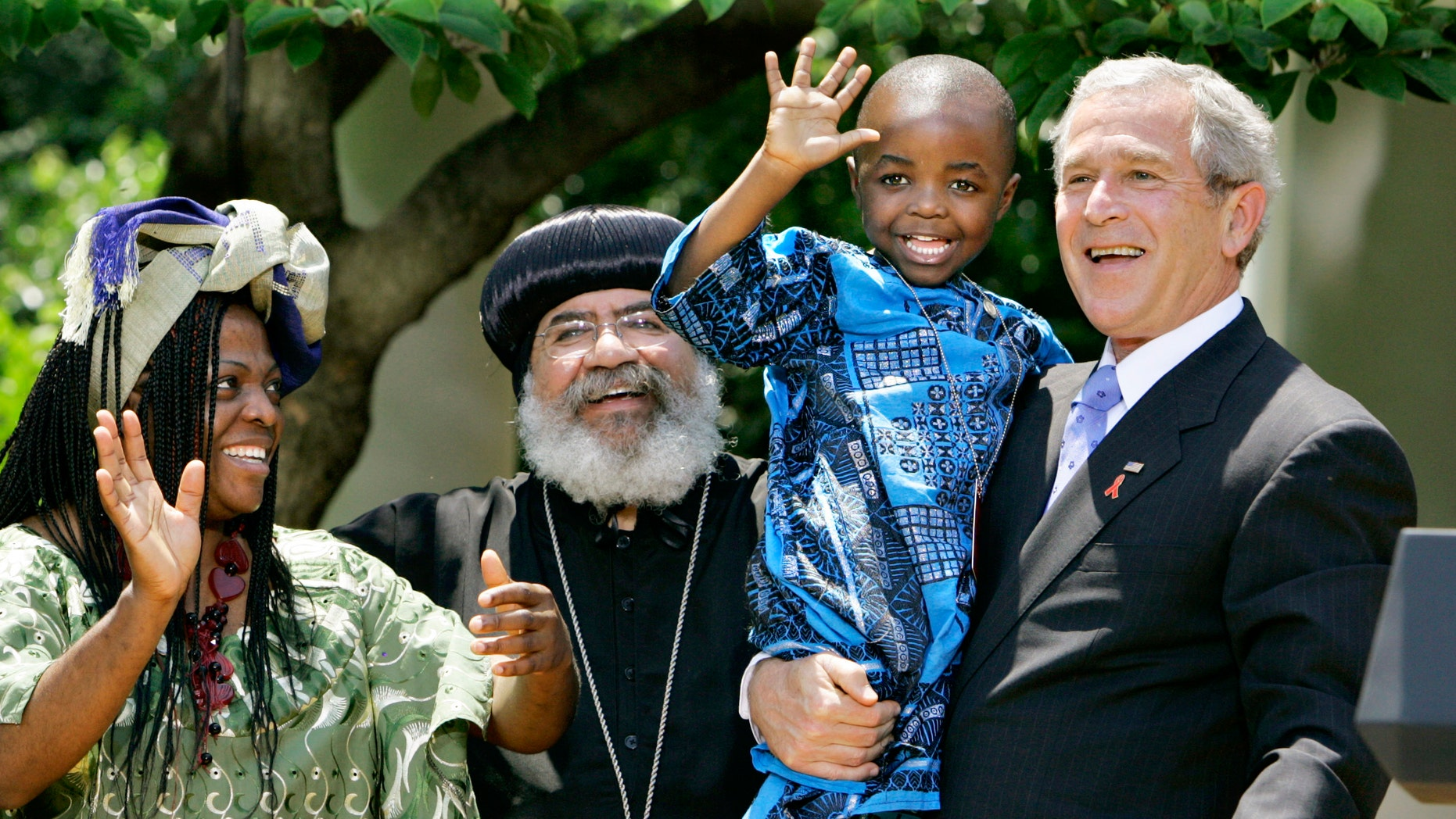 """In this May 30, 2007, file photo President Bush, right, hoists 4-year-old Baron Mosima Loyiso Tantoh, son of Manyongo Mosima """"Kuene"""" Tantoh of South Africa, left, who is HIV-positive, after speaking about his efforts to fight HIV/AIDS worldwide, in the Rose Garden of the White House in Washington."""