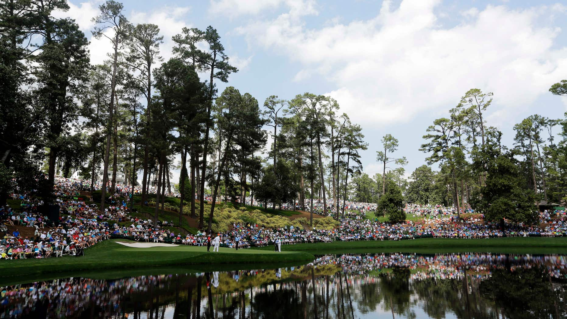April 8, 2015: Spectators sit around the ninth hole during the Par 3 contest at the Masters golf tournament.
