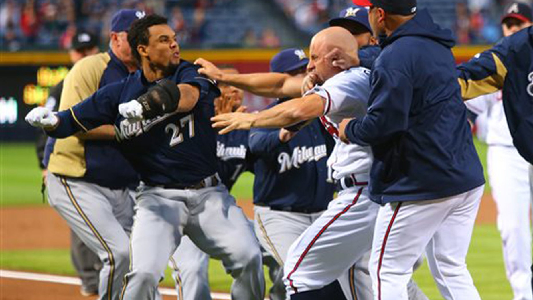 Carlos Gomez, left, and Atlanta Braves Reed Johnson exchange blows following a home run by Gomez on Wednesday, Sept. 25, 2013.