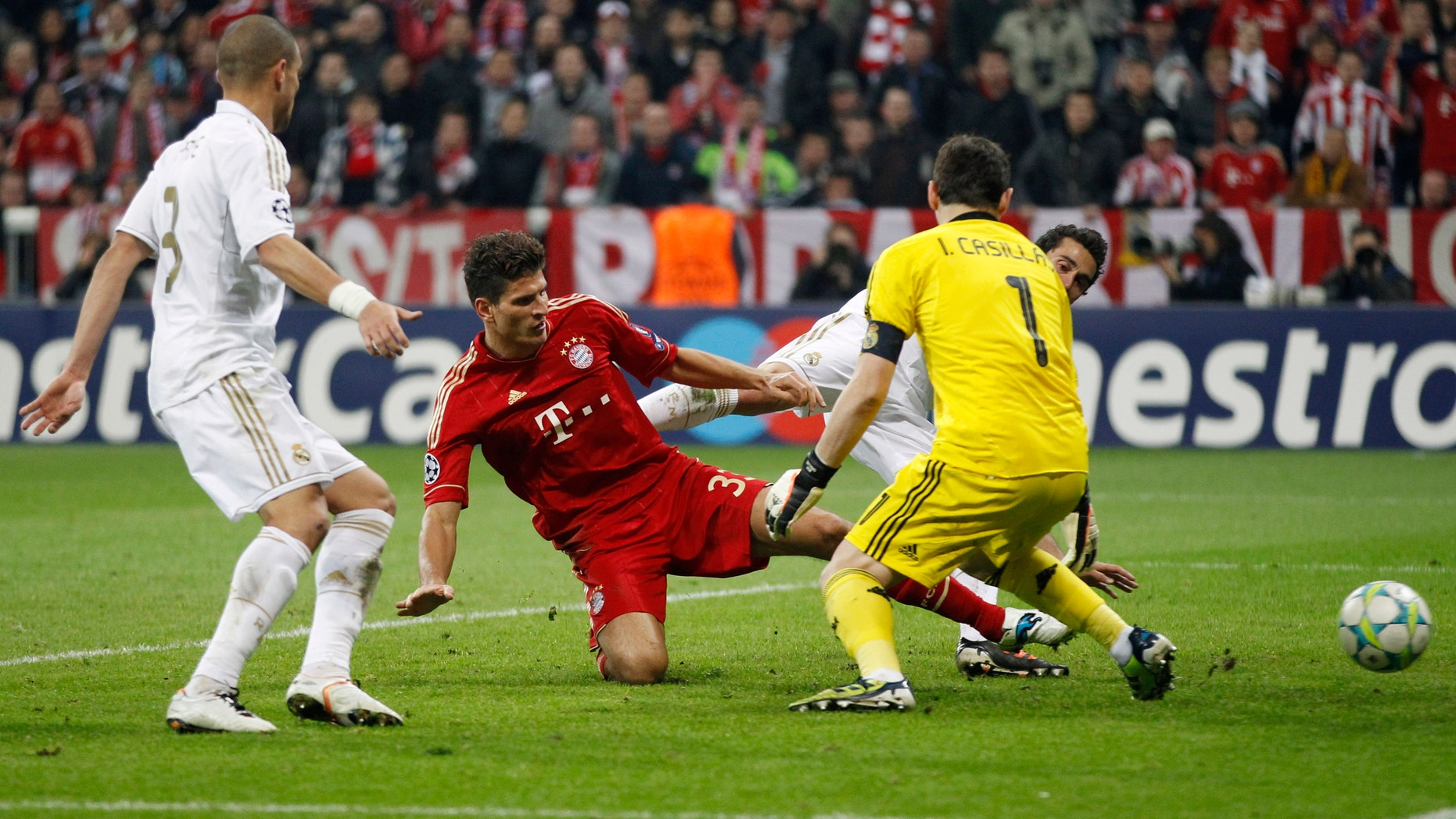 Bayern's Mario Gomez scores his side's 2nd goal past Madrid goalkeeper Iker Casillas, right, during the Champions League first leg semifinal soccer match between Bayern Munich and Real Madrid in Munich, southern Germany, Tuesday, April 17, 2012. (AP Photo/Matthias Schrader)