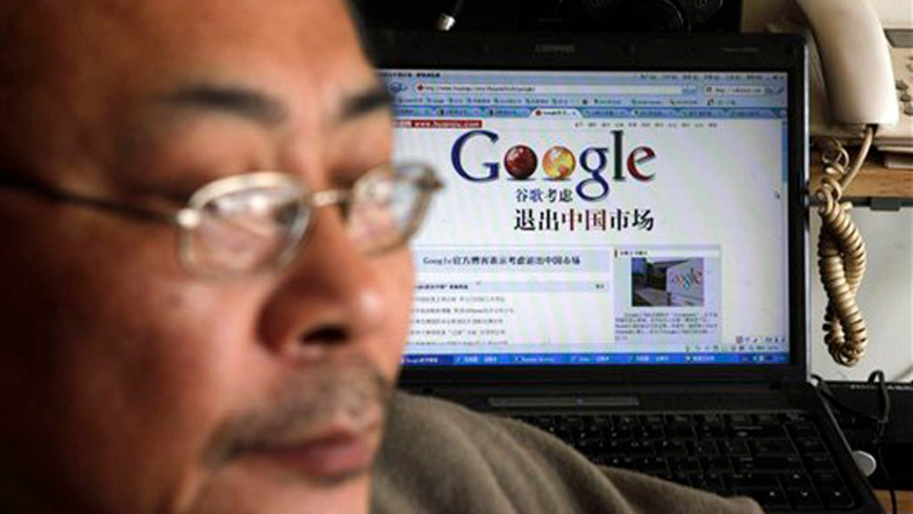 "Award winning Chinese blogger Tiger Temple, or Zhang Shihe, a critic of China's internet censorship, is seen with a webpage with the Chinese words ""Google considers leaving the Chinese market"" in his home in Beijing, Tuesday, March 23, 2010. Google Inc. stopped censoring the Internet for China by shifting its search engine off the mainland Monday but said it will maintain other operations in the country. (AP Photo/ Gemunu Amarasinghe)"