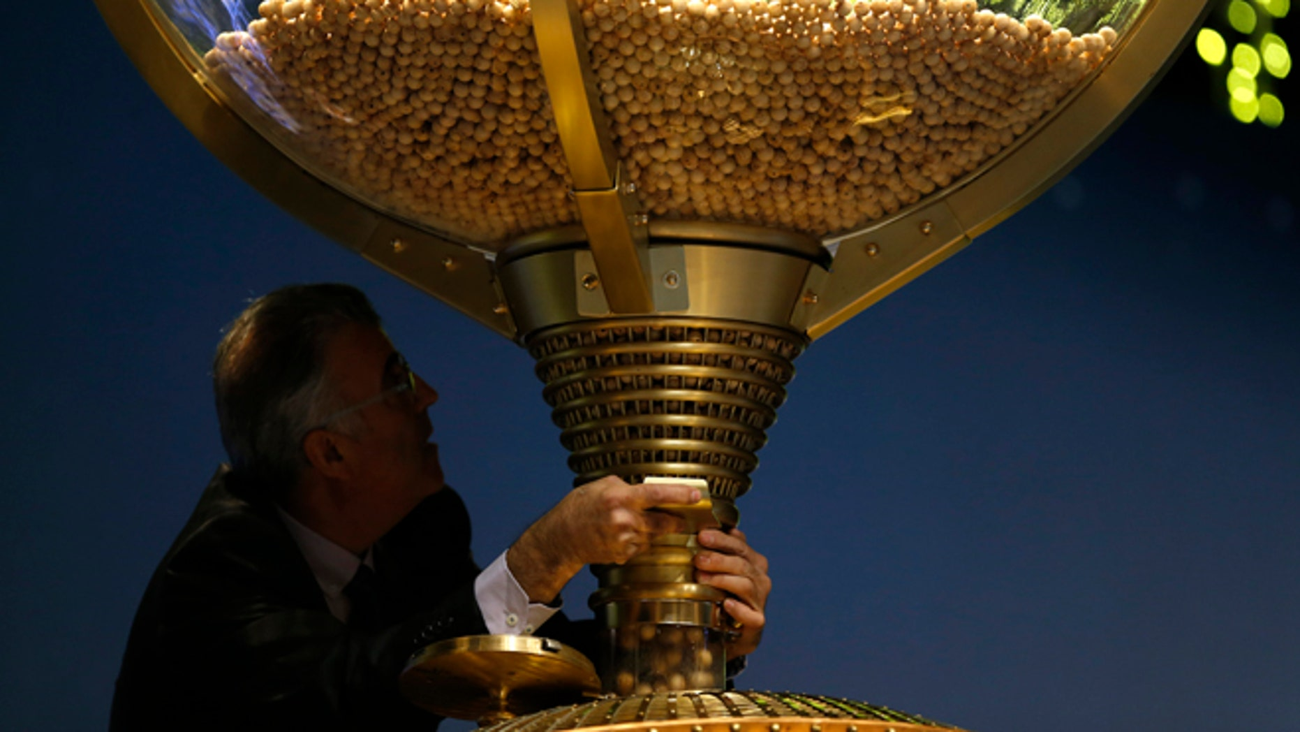 """A worker opens a trap-door in a giant drum to let the balls bearing ticket numbers fall into a lower compartment before the start of Spain's Christmas lottery, in Madrid, Tuesday, Dec. 22, 2015. Celebrations were guaranteed Tuesday in the southern beach town of Roquetas de Mar, southern east Spain, where tickets bearing the top prize number of 79140 in Spain's Christmas lottery, known as """"El Gordo"""" (The Fat One) were sold. The number appeared on 1,600 tickets, known as decimos (tenths) with each holder winning 400,000 euros ($434,800). The tickets are usually sold in many different lottery sales points making it virtually impossible to win the entire 640 million euros assigned to the top prize number. (AP Photo/Francisco Seco)"""