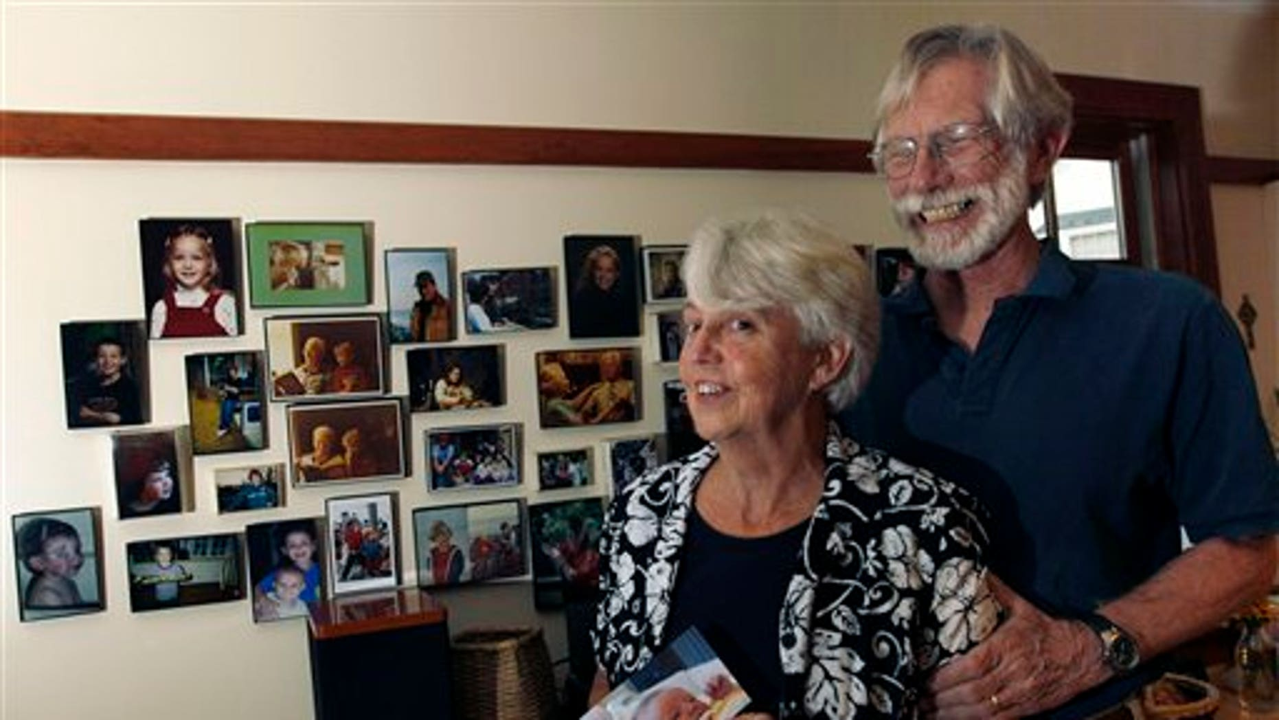 August 24: Eileen and Doug Flockhart laugh as she holds a picture of their seventh grandchild near a wall full of family photos in their home in Exeter, N.H.