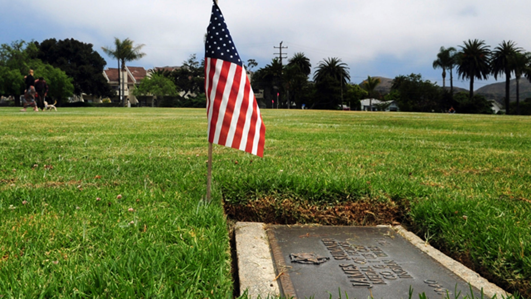 In this undated photo, a couple walks their dog at Memorial Park on East Main Street and Aliso Lane in Ventura, Calif., where several flat headstones dot the terrain including that of James Sumner.