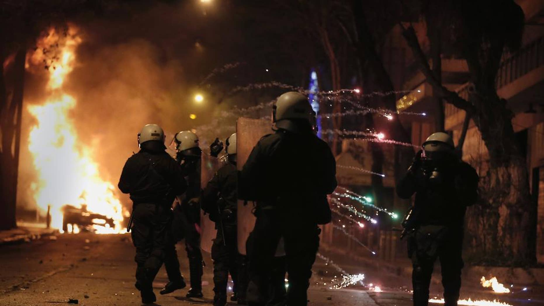 Greek riot police shelter from a flare thrown by rioting youths during clashes after a demonstration by about 700 anarchists seeking the abolition of a maximum security prison, in central Athens, on Tuesday, April 7, 2015. Dozens of rioters burnt at least two cars, smashed a shopfront and threw petrol bombs and stones at police, who responded with tear gas. Four suspected rioters were detained, while no injuries were reported. (AP Photo/Petros Giannakouris)