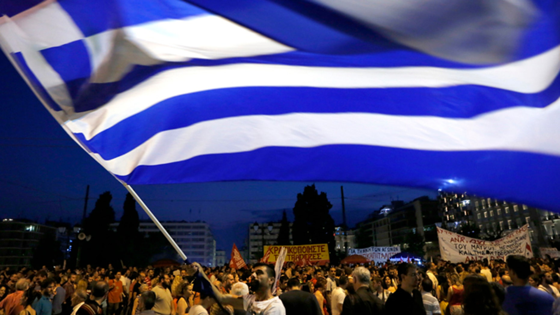 A demonstrator waves a Greek flag during an anti-austerity rally in central Athens, Friday, July 10, 2015. Greek Prime Minister Alexis Tsipras sought his left-wing party's backing on Friday for a new budget austerity package that is harsher than what he urged Greeks to reject in a vote just last week, but would provide the country will longer-term financial support. (AP Photo/Petros Karadjias)