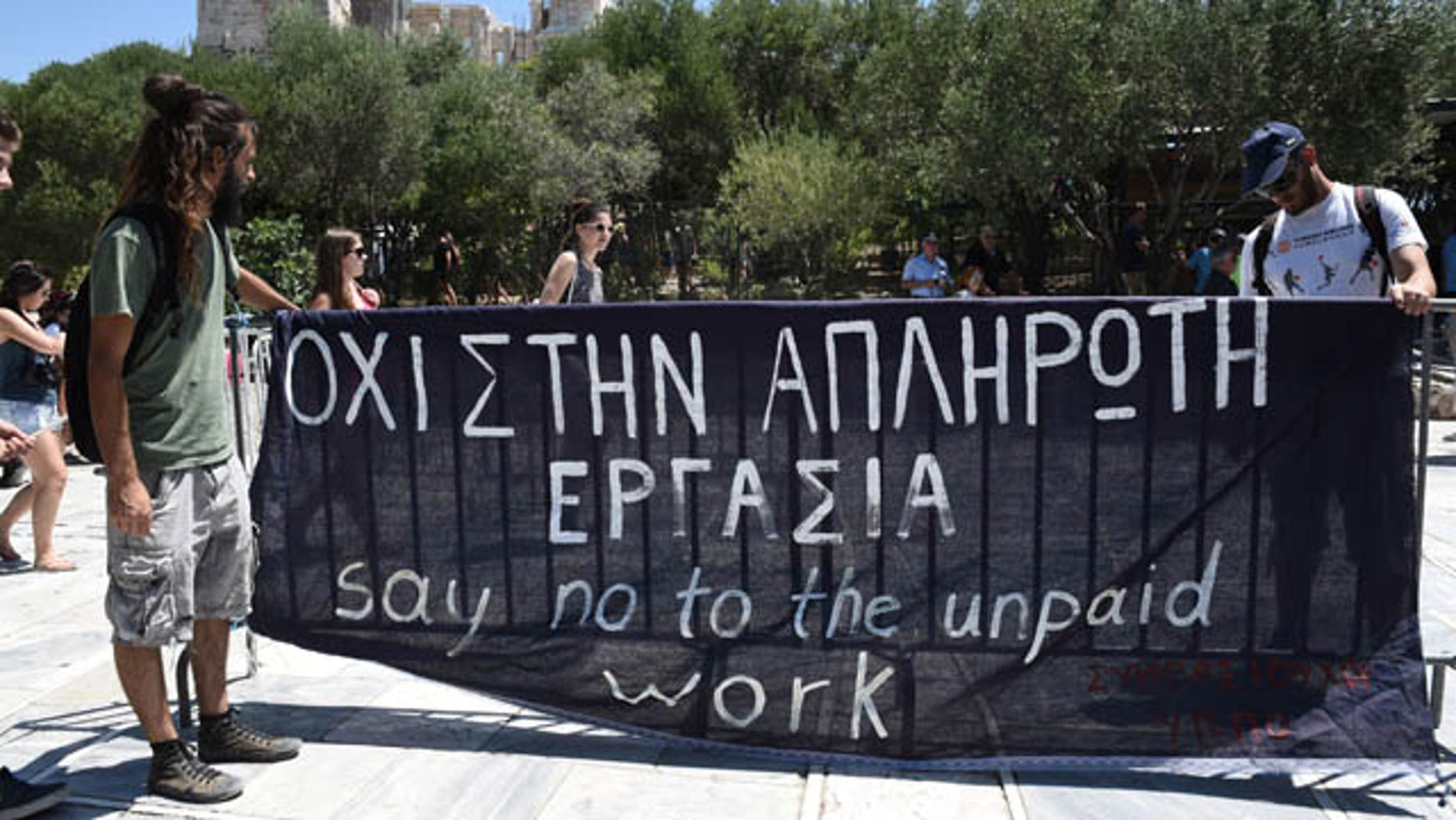 """Short-term contract employees of the Culture Ministry, unpaid for over six months, protest outside the entrance of the ancient Acropolis hill in Athens, Thursday, July 23, 2015. Greece's radical left-led government survived another revolt by rebels in the early hours of Thursday, passing reforms that should pave the way for the imminent start of bailout discussions with European creditors. Sign says in Greek and English """"Say no to the unpaid work."""" (AP Photo/Giannis Papanikos)"""