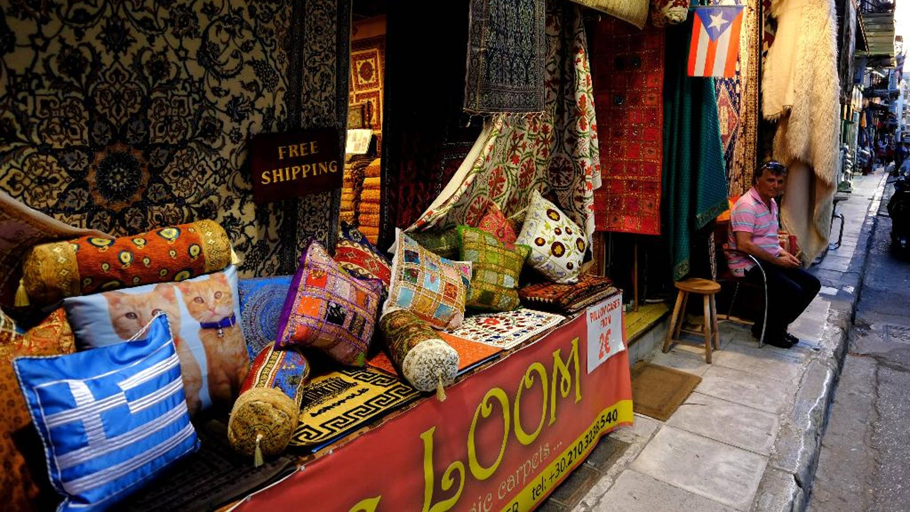 A man sits outside his carpet shop in the tourist district of Plaka in Athens, Friday, June 27, 2014. Tourist arrivals in Greece are expected to increase by 20 percent compared to last year. (AP Photo/Petros Karadjias)