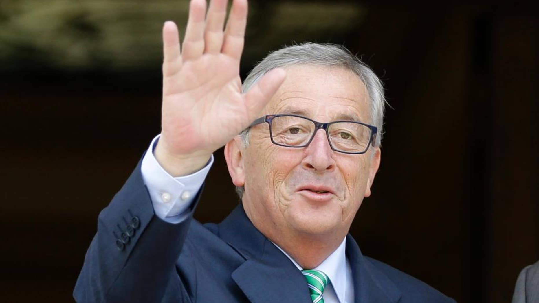 Jean-Claude Juncker, president-elect of the European Commission, left, waves to the media at the Maximos Mansion in Athens, Monday, Aug. 4, 2014. Juncker is visit Athens in his first trip since his election by the new European Parliament last month. He meets Greek Prime Minister Antonis Samaras, a fellow conservative, to express support for the country's ongoing effort to make its public finances sustainable. (AP Photo/Thanassis Stavrakis)