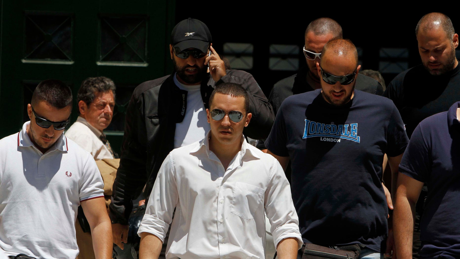 June 11, 2012: The spokesman of Greece's extreme-right Golden Dawn party Ilias Kasidiaris, center, is escorted by party members as they exit the prosecutor's office in Athens.