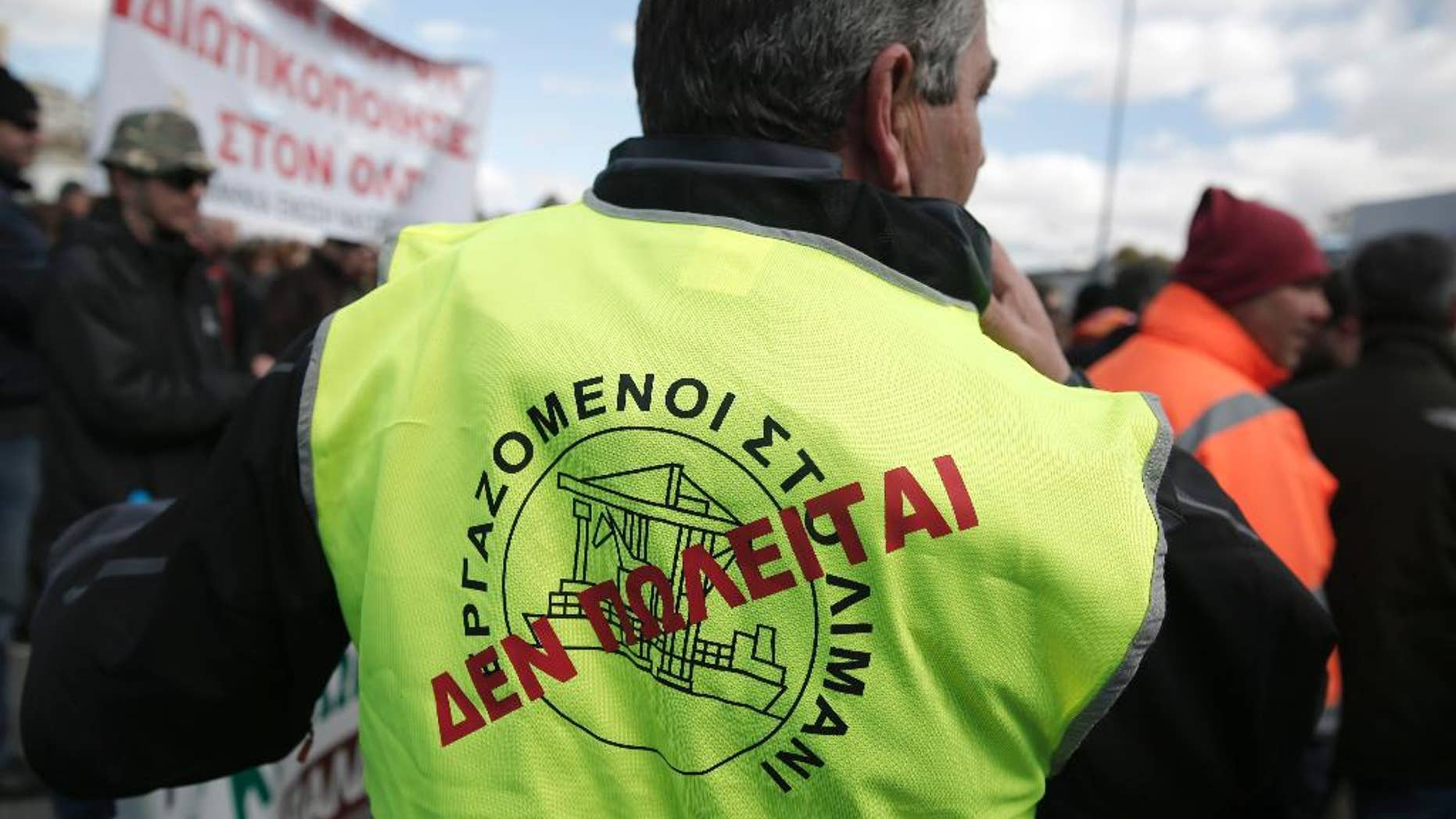 """A dock worker with a """"Not for sale"""" sign on his vest takes part in a protest against government plans to further privatize the harbor of Piraeus, Greece's busiest, in Piraeus, on Tuesday, March 11, 2014. Several hundred people took part in the peaceful demonstration. Once a separate town, Piraeus is now incorporated in the greater Athens area. (AP Photo/Petros Giannakouris)"""