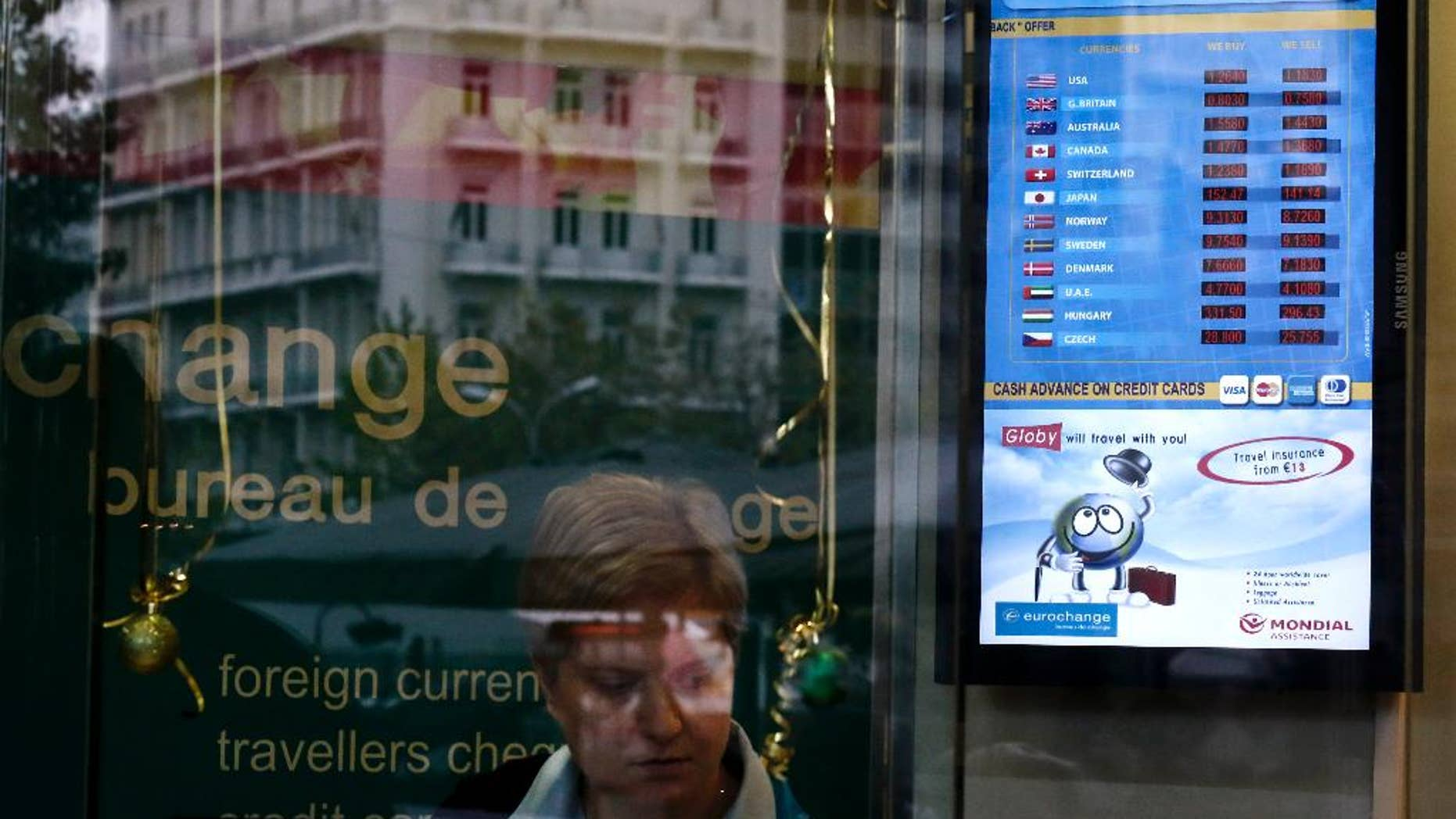 The exchange rate of the US Dollar and the Euro, at top, is displayed in the window of a currency exchange office in Athens, on Monday, Jan. 5, 2015. The euro sank to a nine-year low Monday as new doubts surfaced about Greece's commitment to the common currency bloc. European stocks mostly rose while Asian markets were mixed. (AP Photo/Petros Giannakouris)