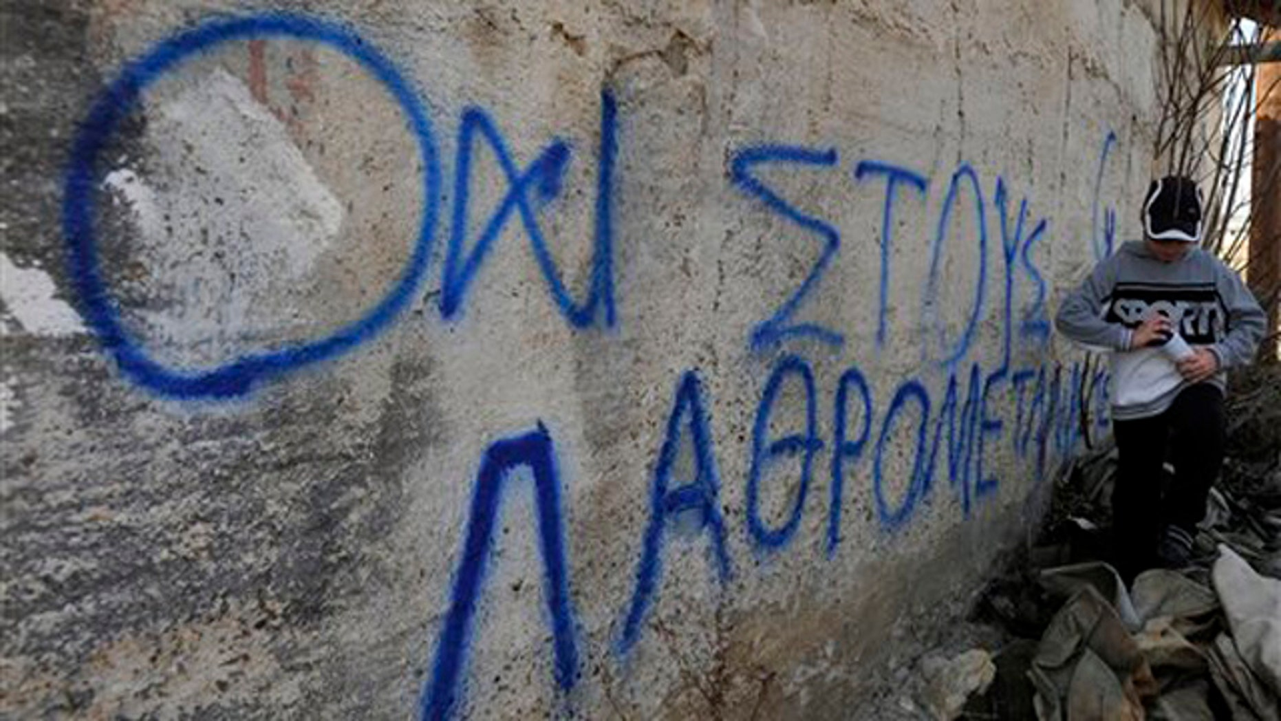 "A boy walks past a spray-painted slogan reading, ""No to illegal immigrants'' on a wall in Neapoli, near the town of Kozani, northern Greece, Friday, March 23, 2012. Residents of a northern Greek town erected barricades and vowed Friday to man them round the clock to prevent authorities from turning a disused army base into the country's first major detention center for illegal immigrants. (AP Photo/Nikolas Giakoumidis)"