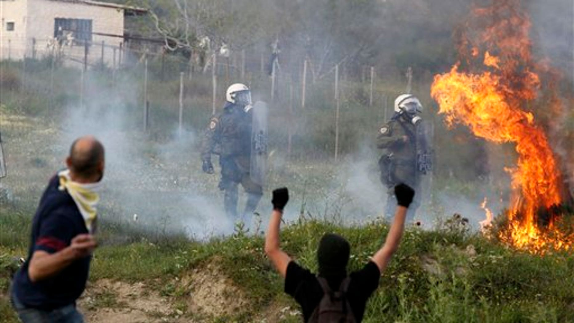 April 14: Protesters attack with gas bombs and stone against riot police during clashes in the town of Keratea, about 31 miles southeast of Athens. Greek protesters have used excavators to cut a shoulder-high trench on a busy road near a proposed new landfill, cutting off traffic outside Athens. Youths clashed later Thursday at the site with riot police, who responded with tear gas. (AP)
