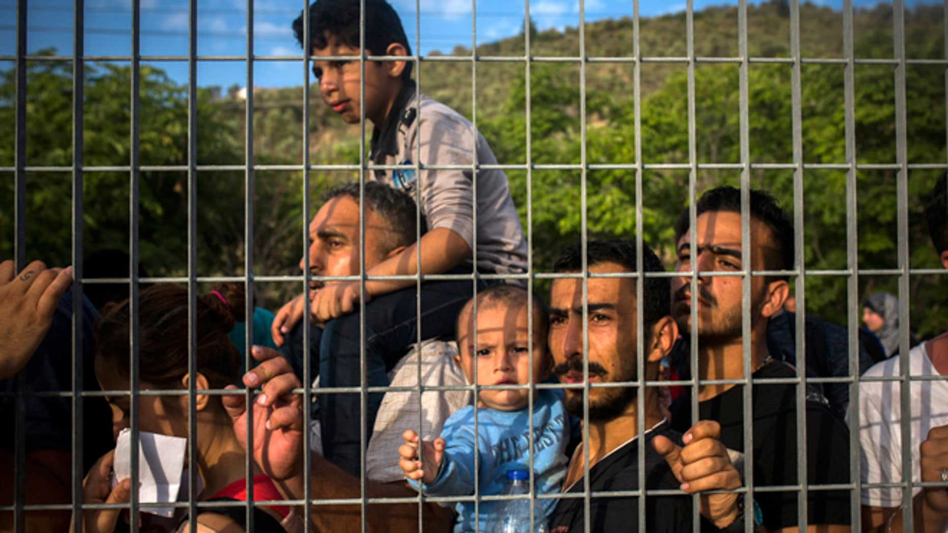 Sept. 8, 2015: Refugees and migrants wait for their registration and the issuing of travel documents at a soccer stadium in Mytilene, Greece.