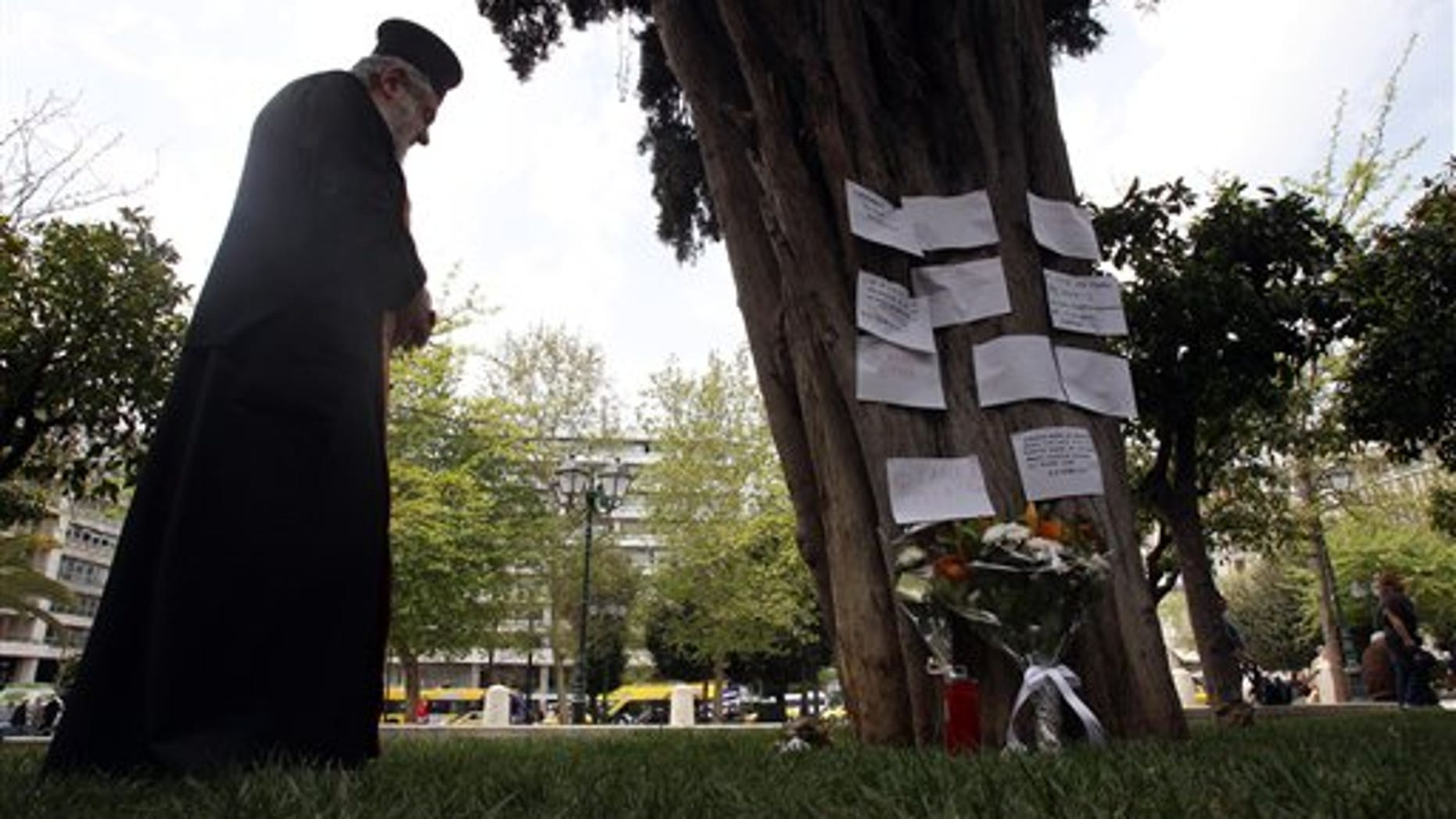 April 4, 2012: A Greek Orthodox priest holds a memorial service, at the site where an elderly man fatally shot himself at Athens' main Syntagma square.