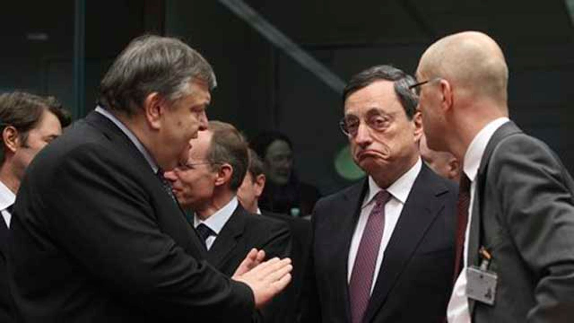Feb. 20, 2012: Greek Finance Minister Evangelos Venizelos, left, gestures while speaking with European Central Bank President Mario Draghi, second right, during a round table meeting of eurozone finance ministers at the EU Council building in Brussels.