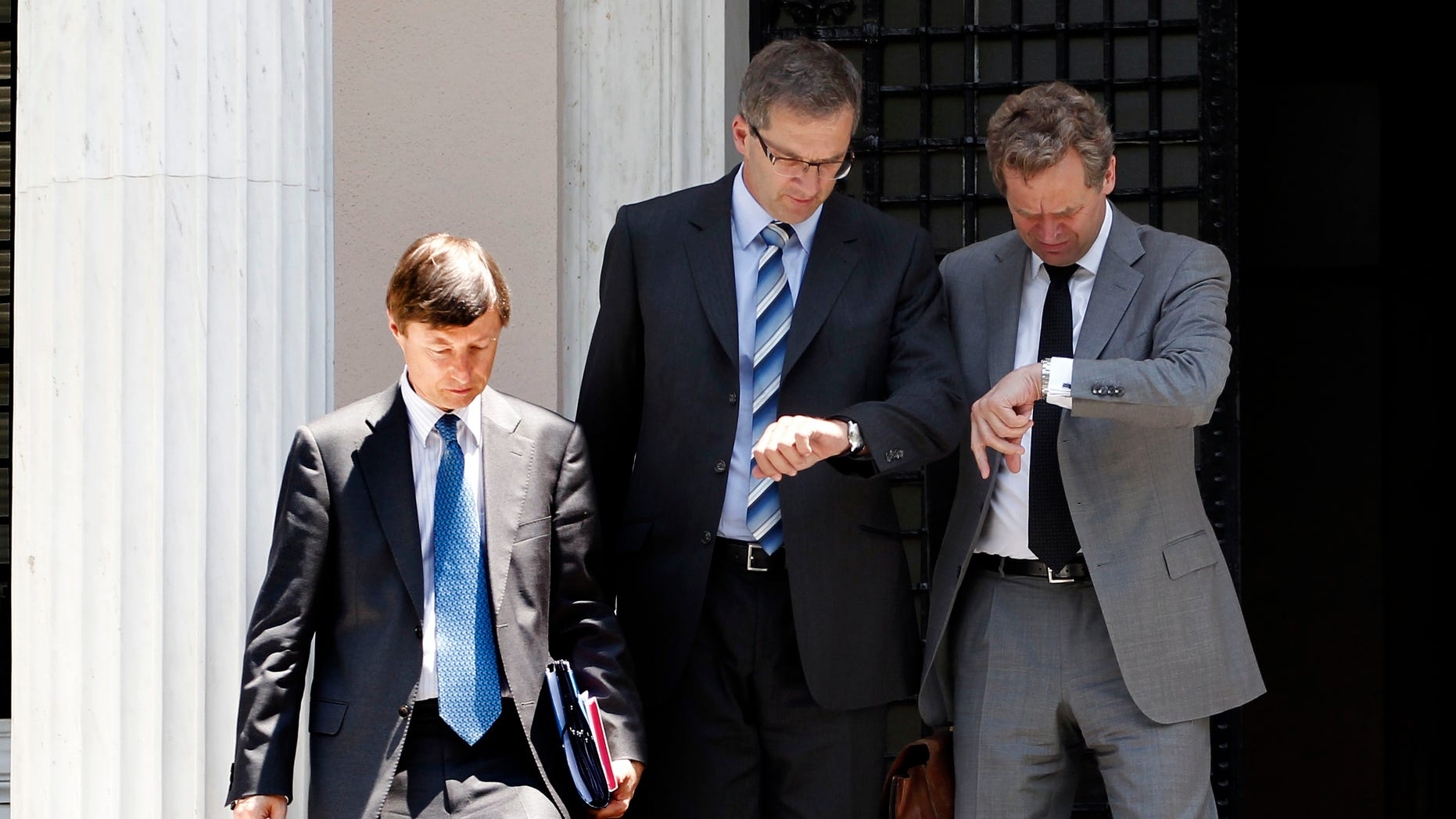 Poul Thomsen, the International Monetary Fund mission chief in Greece, right, and Klaus Masuch of the European Central Bank, center, check their watches next to European Commission official Matthias Mors as they leave Maximou mansion after a meeting with Greek Prime Minster Antonis Samaras, in Athens, Thursday, July 5, 2012. The debt inspectors from the European Central Bank, European Commission and International Monetary Fund, known as the troika, were meeting the new government, whose coalition partners want to persuade the country's rescue creditors to ease some of the strict terms of its bailout. (AP Photo/Petros Giannakouris)