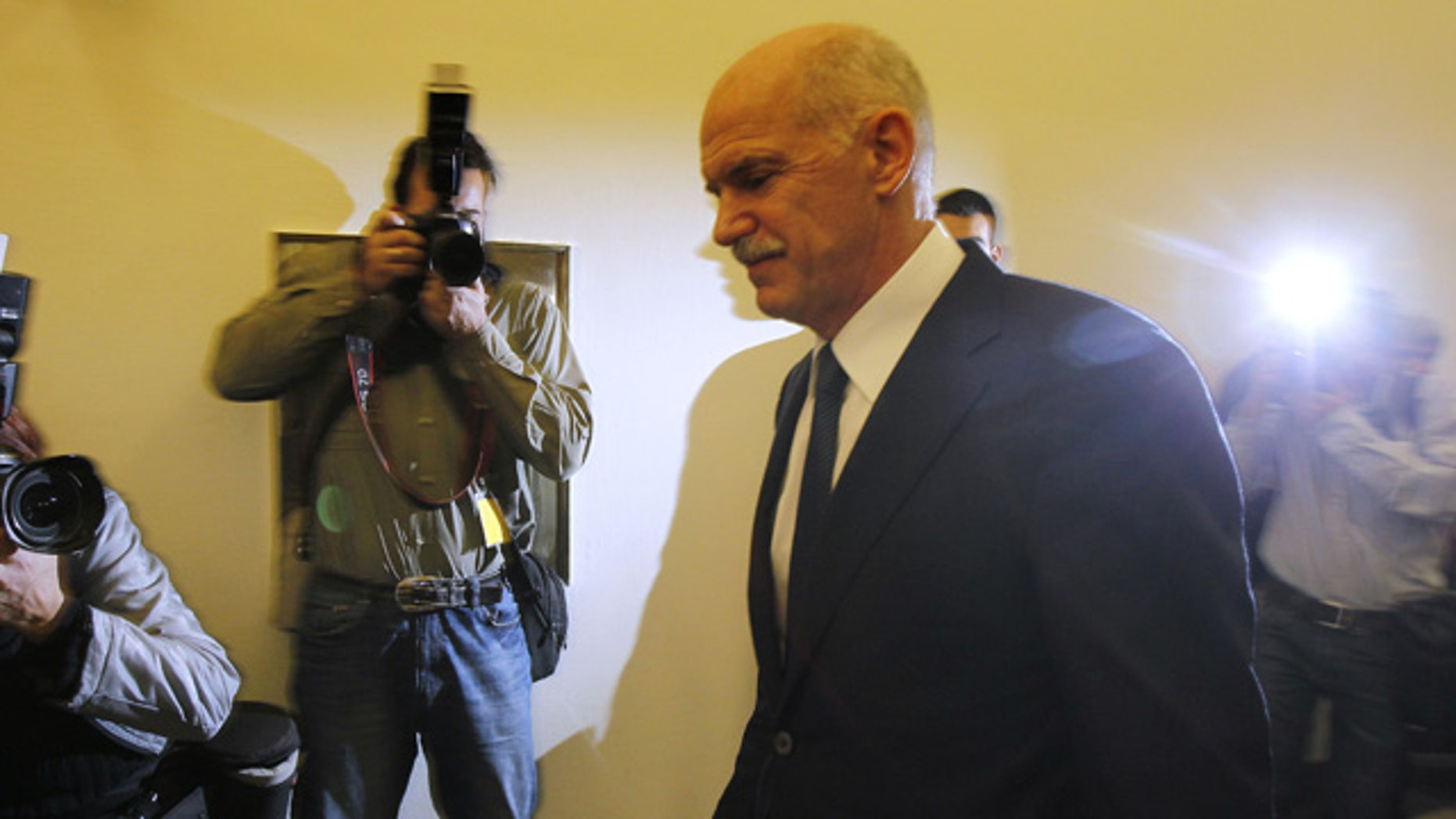 Greek Prime Minister George Papandreou returns to an emergency cabinet meeting after he took a short break at the Greek parliament in Athens, on Thursday, Nov. 3, 2011. A spokesman for Greece's government says it is prepared to discuss an opposition demand for the creation of a transitional government to approve the latest European bailout deal and secure the next installment of rescue loans for the country. (AP Photo/Thanassis Stavrakis)