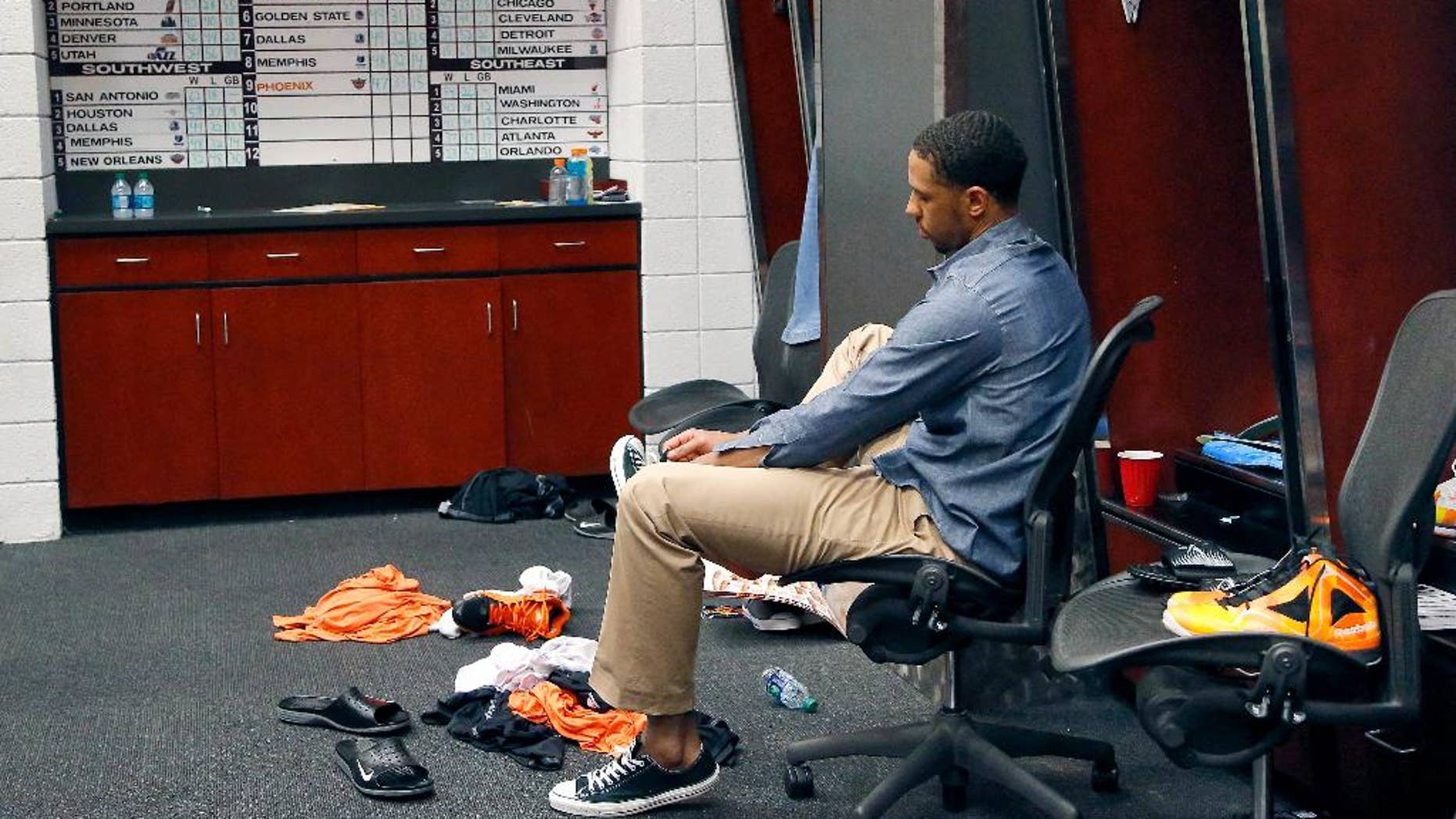 Phoenix Suns' Channing Frye laces up his shoe in the locker room after an NBA basketball game against the Memphis Grizzlies, Monday, April 14, 2014, in Phoenix. The Grizzlies won 97-91 eliminating the Suns from the playoffs. (AP Photo/Matt York)