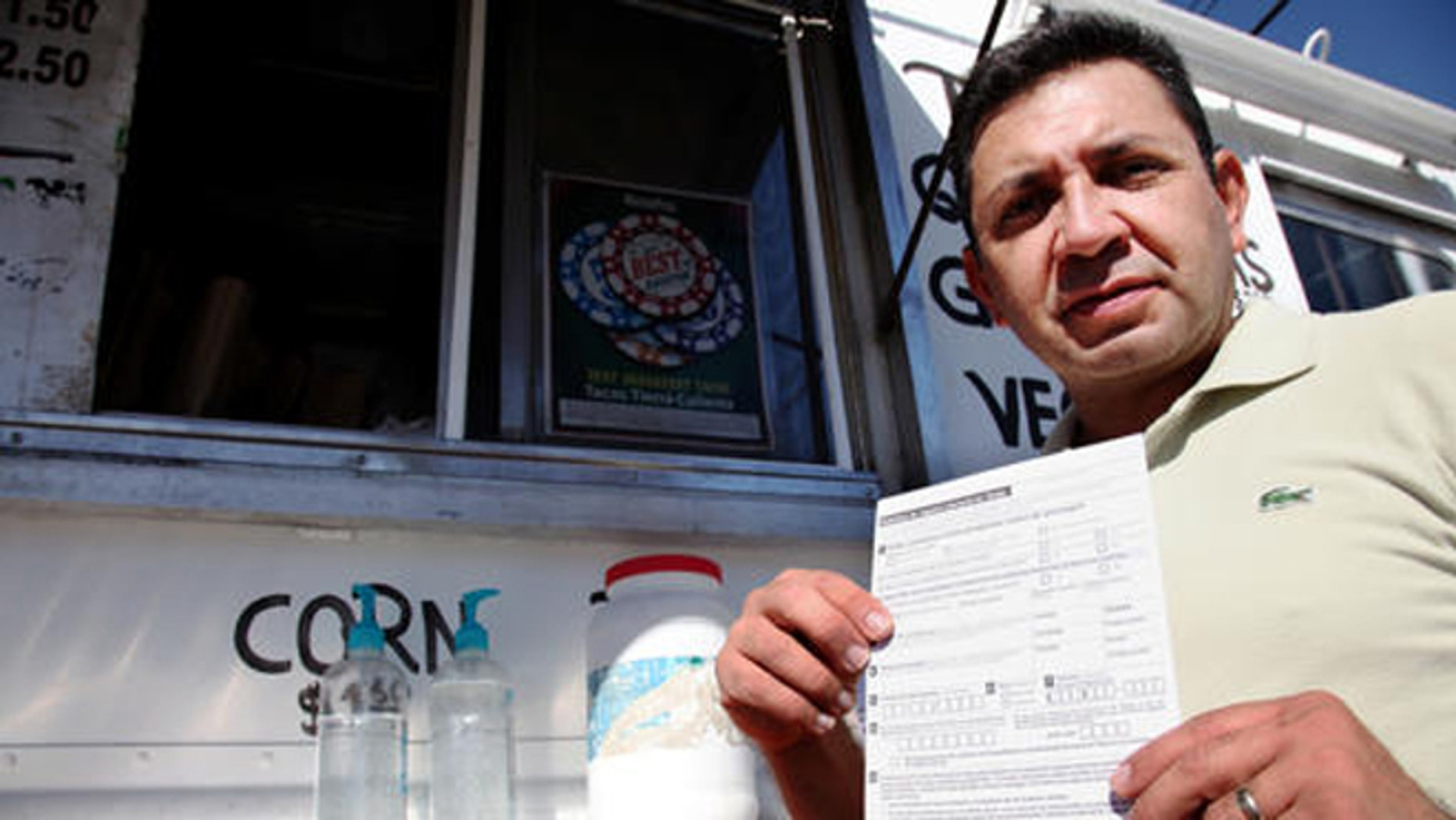 """Carlos Zamora shows a voter registration card from a pile placed on the counter of the Tierra Caliente taco truck on Thursday, Sept. 29, 2016, in Houston. Zamora is with Mi Familia Vota, a Latino activist group that seeks to register more voters in the Latino community. Mi Familia Vota partnered with a local design firm to make eight of the city's taco trucks into mobile voter registration booths after a surrogate of Republican presidential candidate Donald Trump recently suggested that unless the United States fortifies its borders and tightens immigration limits, """"You're going to have taco trucks on every corner."""" (AP Photo/John L. Mone)"""