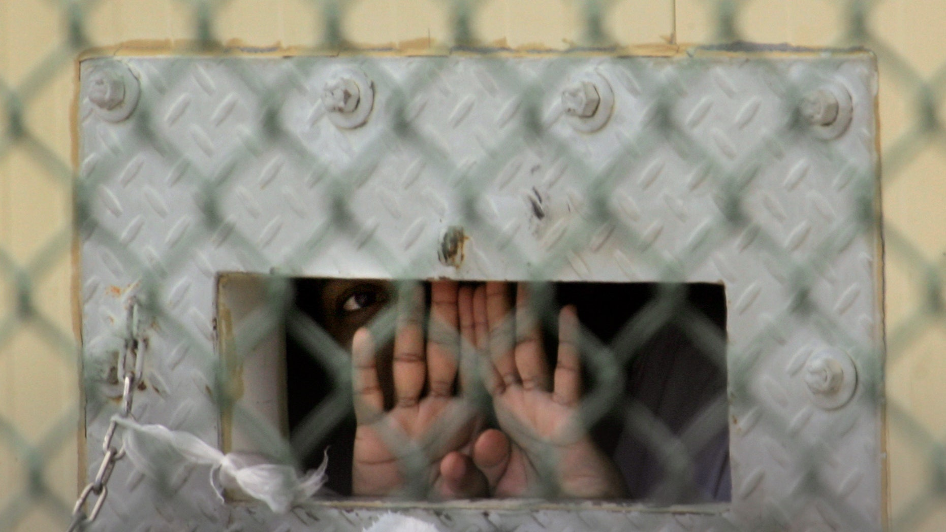 "In this file photo reviewed by a U.S. Dept of Defense official, a detainee shields his face as he peers out through the so-called ""bean hole"" which is used to pass food and other items into detainee cells, at Camp Delta detention center, Guantanamo Bay U.S. Naval Base, Cuba."