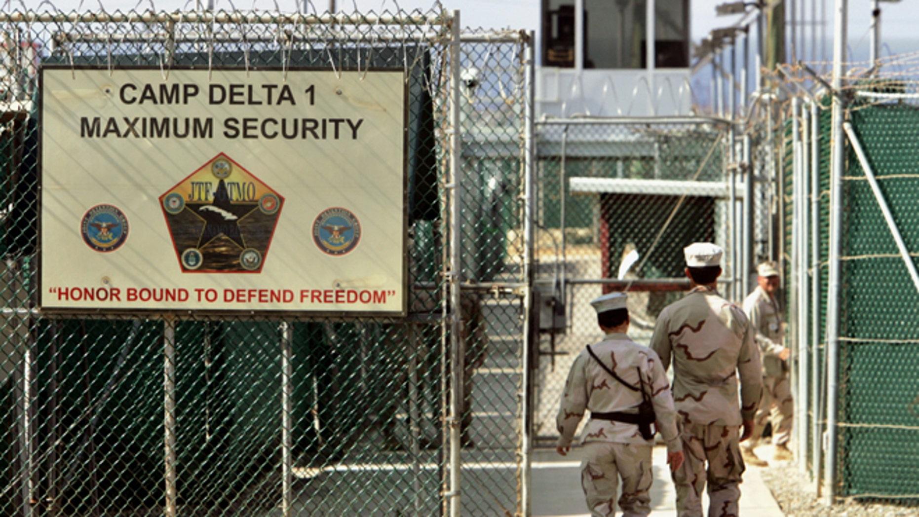 FILE: 2006: U.S. military guards walk within Camp Delta military-run prison, at the Guantanamo Bay U.S. Naval Base, Cuba.