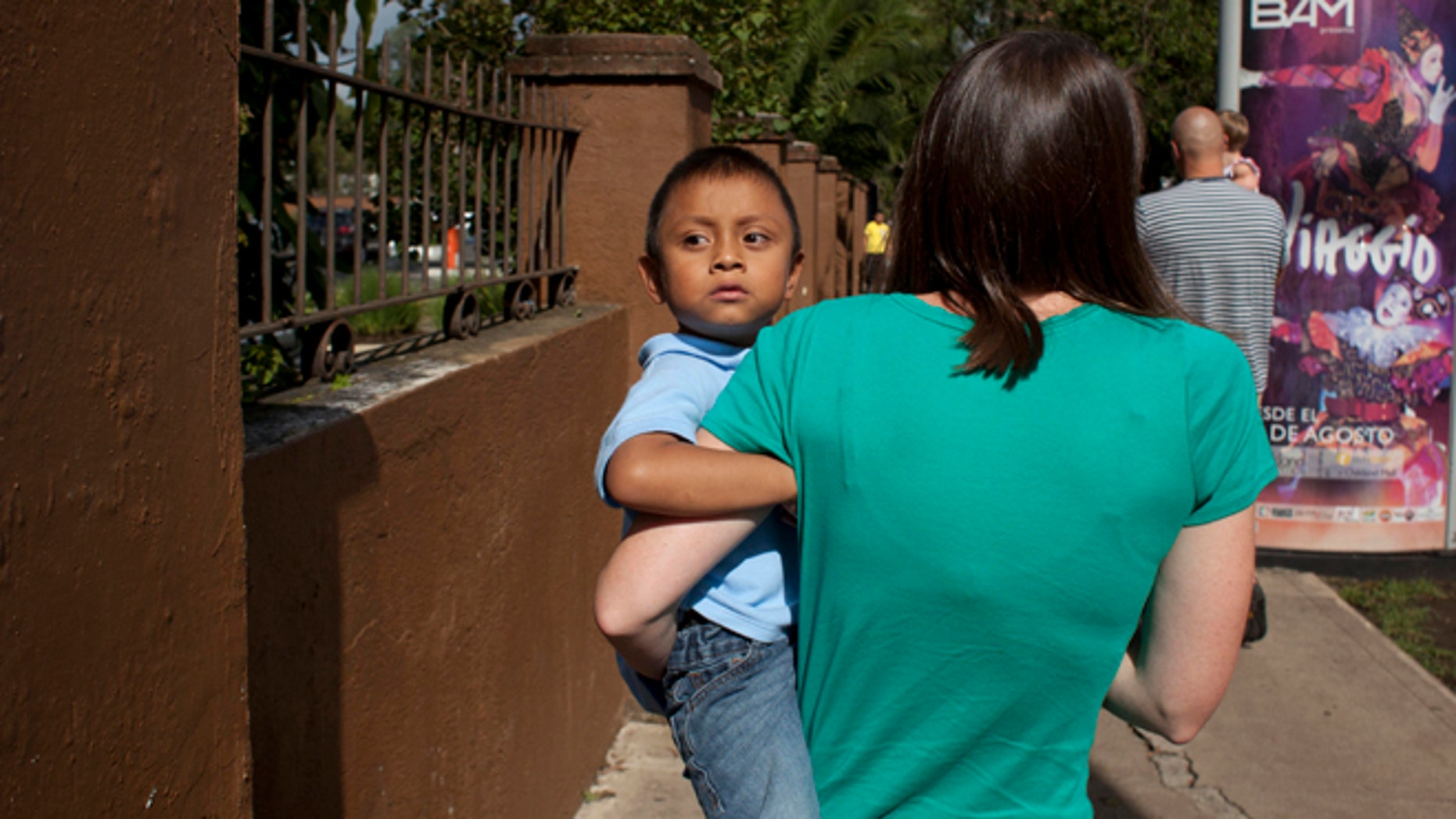 In this Friday, Sept. 7, 2012 photo, Jessica Hooker, left, carries her adopted son Daniel in Guatemala City. (AP Photo/Moises Castillo)