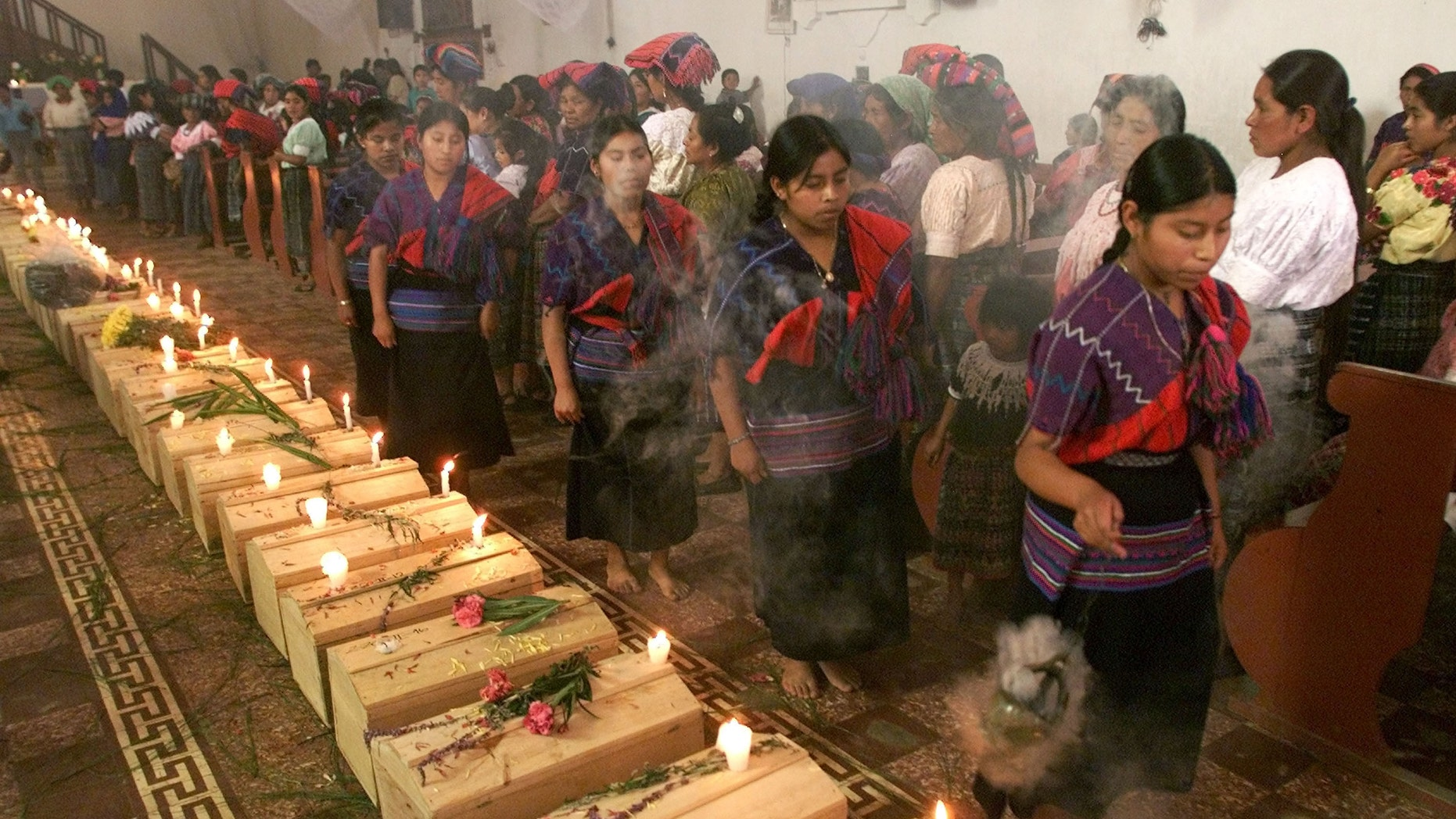 391523 03: Guatemalan Mayan Quiche Indian women dance and burn incense around 41 coffins of victims, found in a 1980''s clandestine cemetery, during mass July 5, 2001 in Zacualpa, Quiche, 150 miles northwest of Guatemala''s capital. According to the Guatemalan Anthropology Forensic Foundation, the cemetery is just one of 669 that has resulted from a 36-year civil war that left 200,000 missing people in the country. (Photo by Andrea Nieto/Getty Images)
