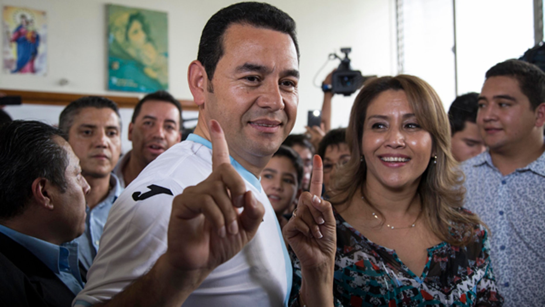 Oct. 25, 2015: Jimmy Morales, the National Front of Convergence party candidate, wearing the Guatemalan national soccer team jersey, accompanied by his wife Hilda Patricia Morales, show their inked fingers after casting their votes during the presidential runoff election at a polling station in Mixco, Guatemala. (AP Photo/Luis Soto)