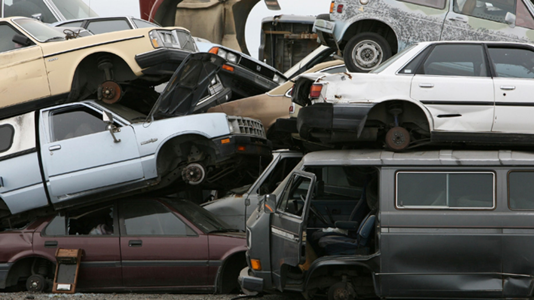 """RICHMOND, CA - JULY 31:  Junk cars are seen stacked at Deal Auto Wrecking July 31, 2009 in Richmond, California. Federal lawmakers are seeking an additional $2 billion to keep the popular """"Cash For Clunkers"""" program going after the initial $1 billion in funding ran out after a week.  (Photo by Justin Sullivan/Getty Images)"""