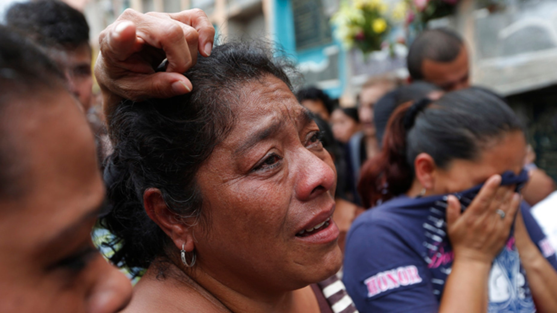 Relatives weep during the burial of Amilcar Estrada and his 10-year-old niece Maria Jose, who died in a mudslide, in the Santa Catarina Pinula cemetery on the outskirts of Guatemala City, Sunday, Oct. 4, 2015. Rescue workers recovered more bodies Saturday after a hillside collapsed on homes late Thursday, while more are feared still buried in the rubble. (AP Photo/Moises Castillo)