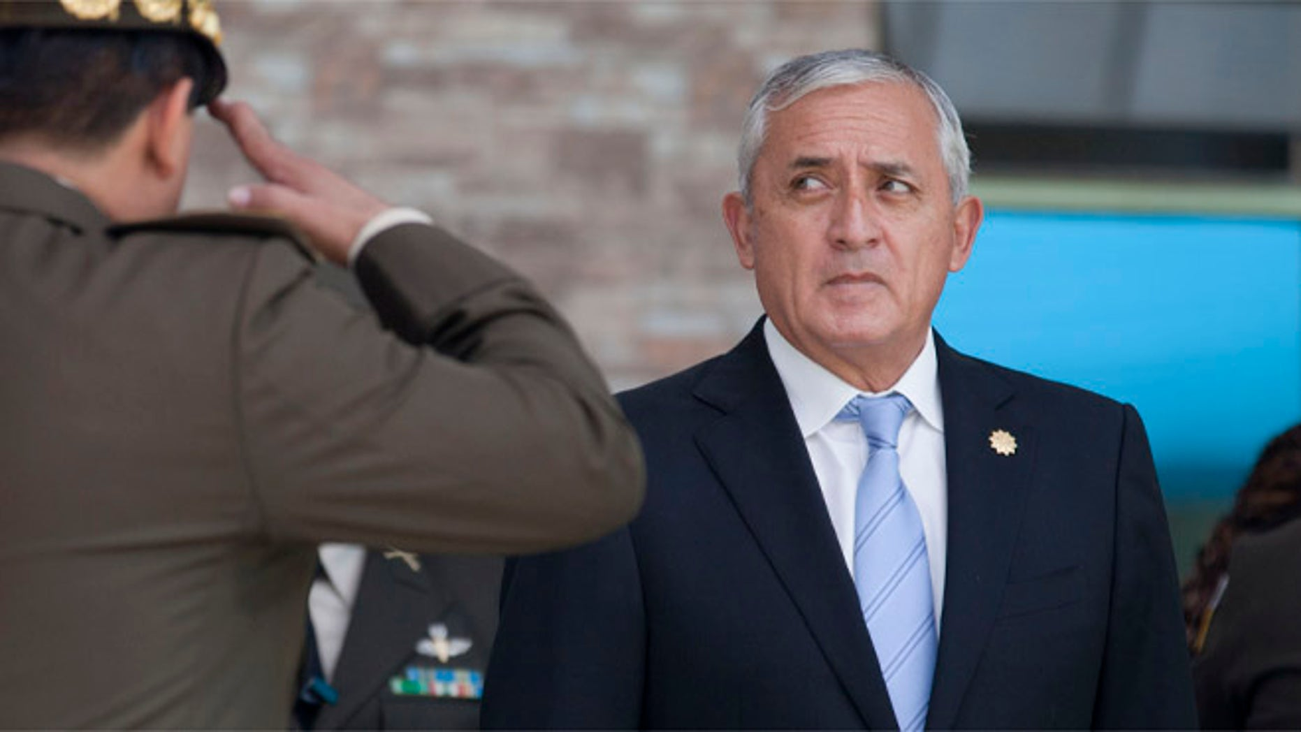 FILE - In this Aug. 14, 2015 file photo, a soldier salutes Guatemala's President Otto Perez Molina during a swearing-in ceremony for his newly-named defense minister, in Guatemala City. The attorney generalâs office of Guatemala issued a statement, urging the embattled leader to step down. The office said in a statement posted on its website late Wednesday, Aug. 26, 2015, that Perez Molina should âsubmit his resignation, to prevent ungovernability.â (AP Photo/Moises Castillo, File)