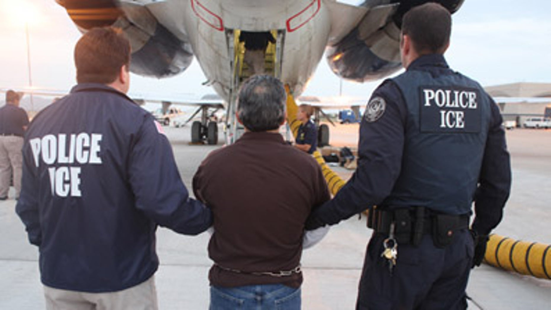 "This image provided by U.S. Immigration and Customs Enforcement (ICE) shows Pedro Pimentel Rios being led to a  government-chartered plane to Guatemala at an ICE airport in Mesa, Ariz. on Tuesday, July 12, 2011. Pimentel, a former instructor at the Guatemalan training school for a force known as the ""kaibiles,"" was ordered deported from the United States in May when an immigration judge rejected his bid for asylum. (AP Photo/ICE)"