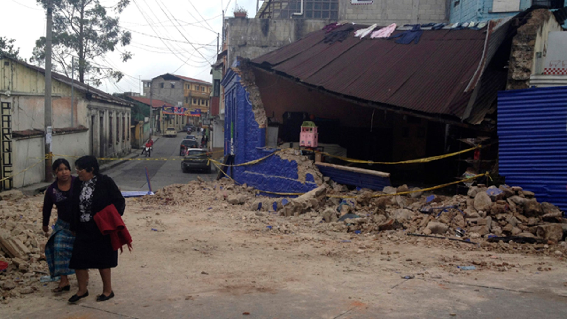 Nov. 7, 2012: Two women walk past a building damaged after a magnitude 7.4 earthquake struck in San Marcos, Guatemala.