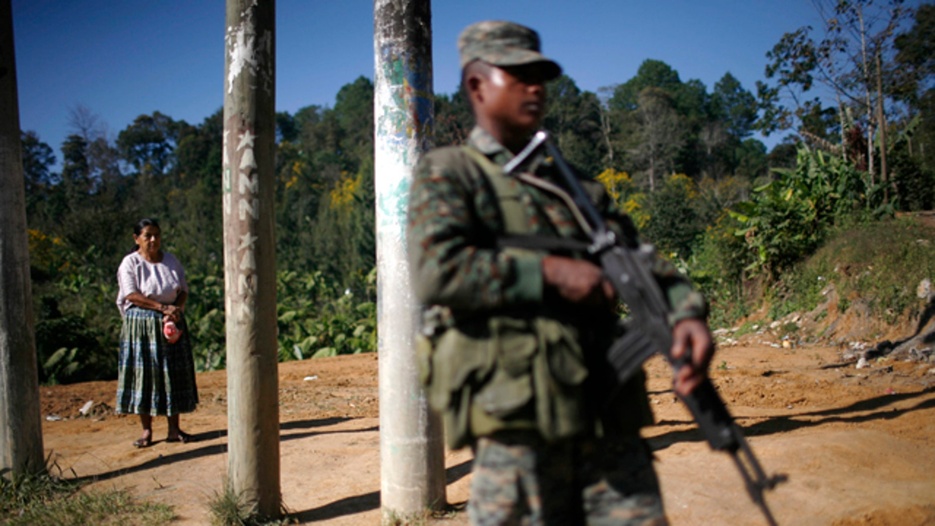 A woman waits for a bus as a soldier stands guard at a checkpoint in Coban, Guatemala, Tuesday Dec. 21, 2010.  The Guatemalan military declared a monthlong state of siege Sunday in Alta Verapaz in hopes of reclaiming cities that have been taken over by Mexico's brutal Zetas drug gang. Local leaders of the mountainous northern province, which has become a prime corridor for smuggling drugs from Honduras to Mexico, say they have been asking state and federal authorities to intervene for two years now. (AP Photo/Rodrigo Abd)