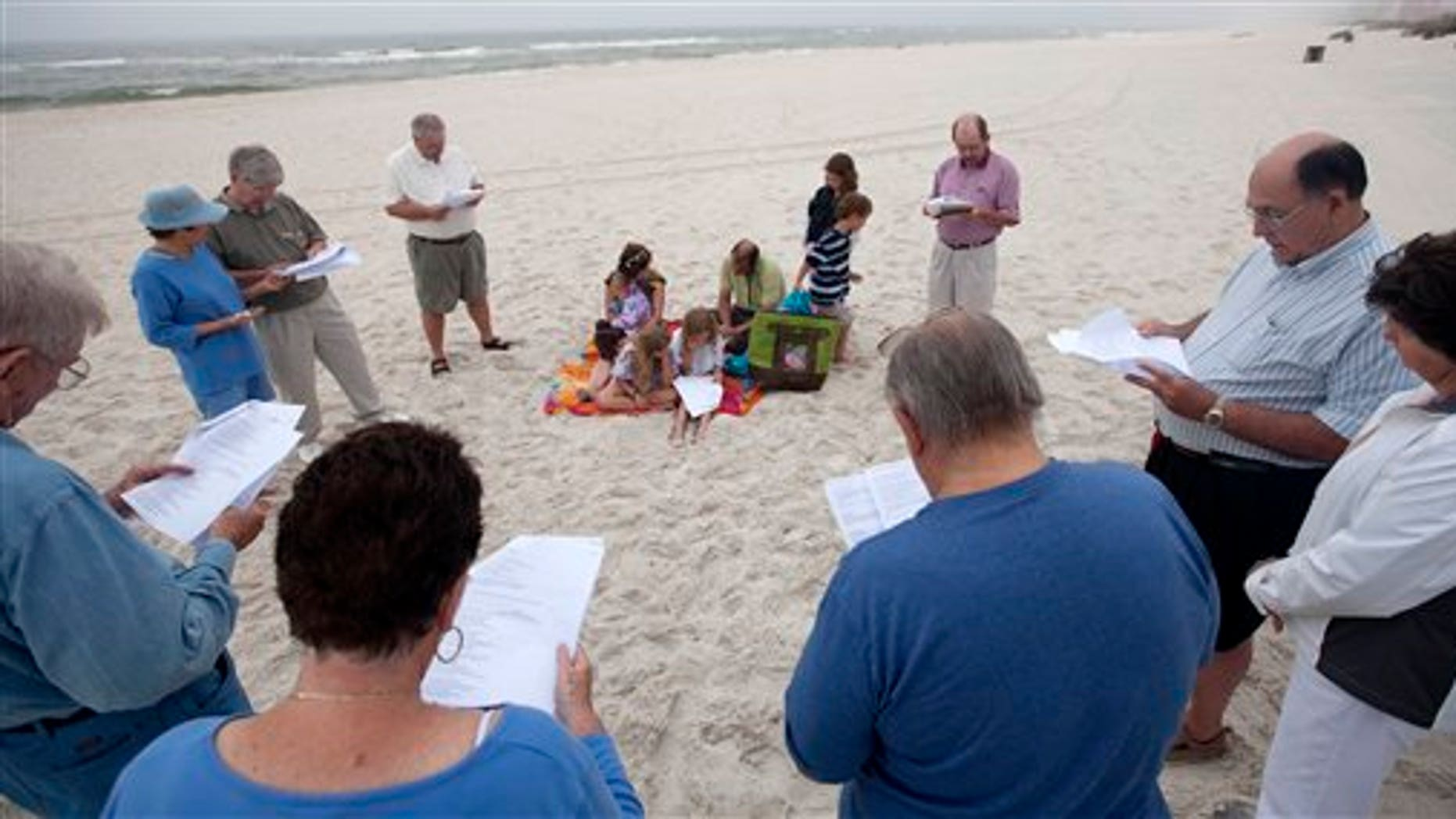 April 20: People gather in prayer at dawn during a prayer vigil for those who suffered following the Deepwater Horizon incident in Orange Beach, Ala.