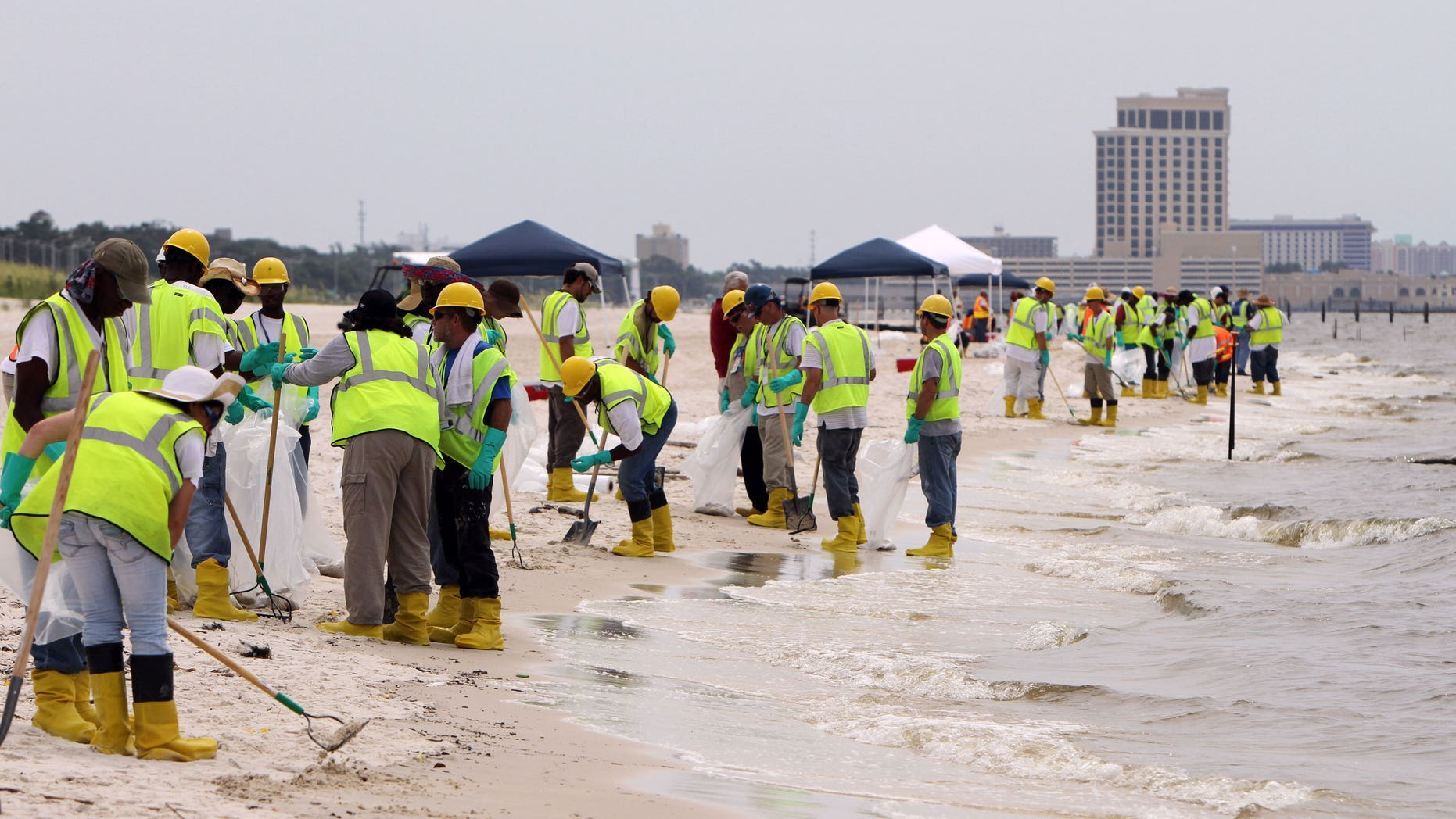 June 28: About three hundred BP contract workers tend to the beaches in Biloxi, Miss., to remove tar balls that had washed ashore over the weekend. (AP)