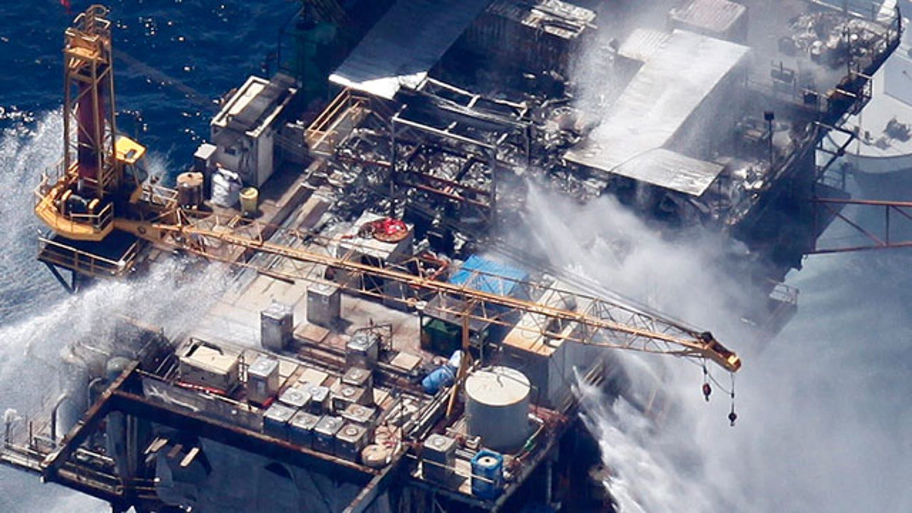 Boats are seen spraying water on an oil and gas platform that exploded in the Gulf of Mexico, off the coast of Louisiana., Thursday, Sept. 2, 2010. All 13 crew members were rescued.