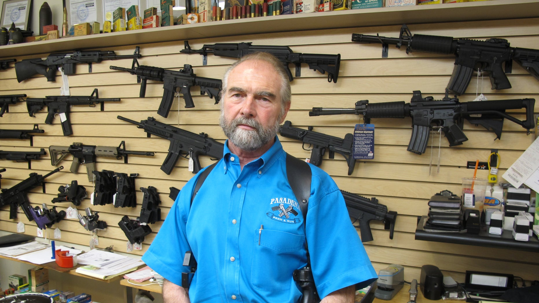 Sept. 26, 2013: Frank Loane, owner of Pasadena Pawn and Gun, stands in front of a wall of assault rifles at his store in Pasadena, Md.