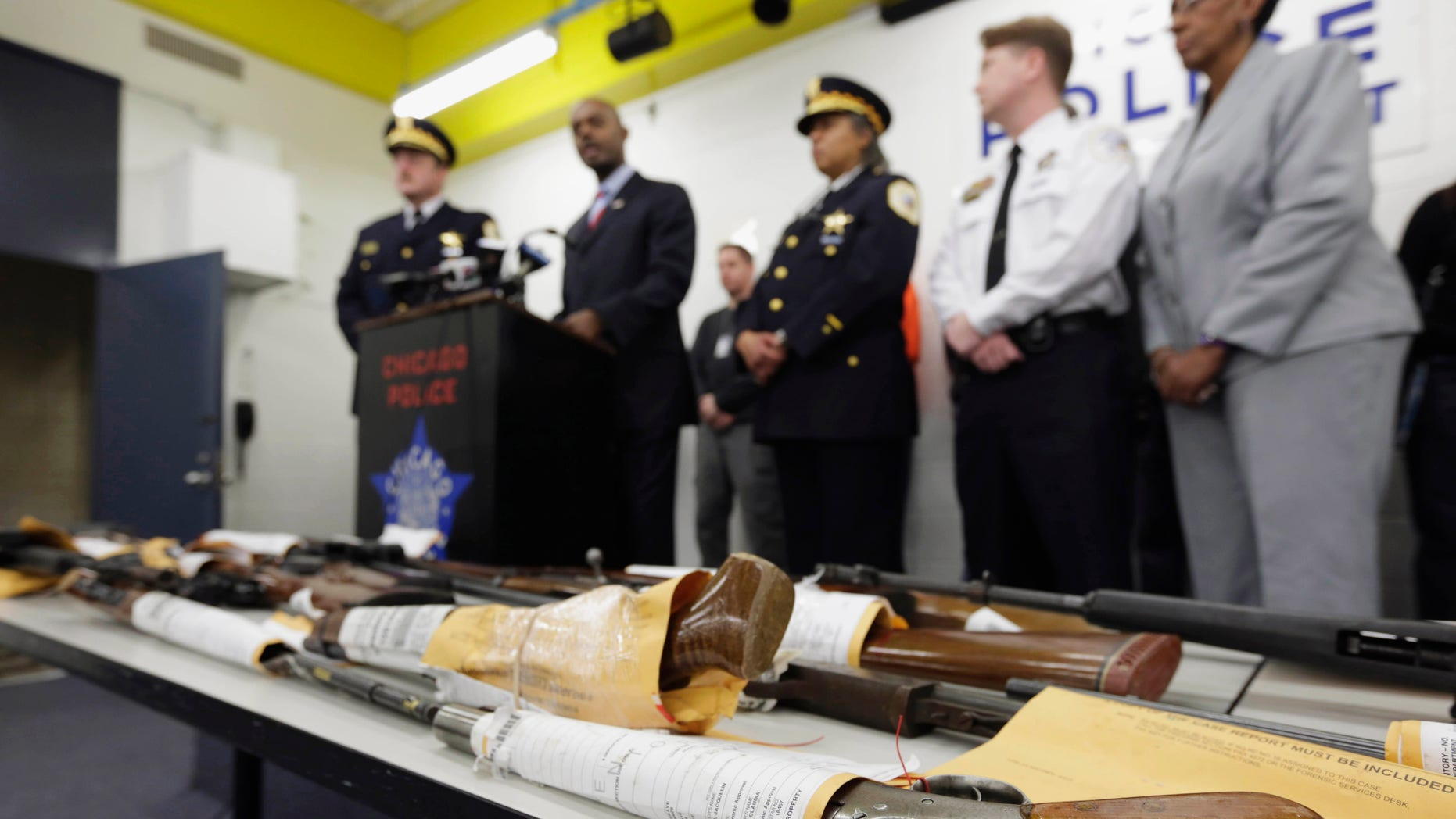 FILE - In this Jan. 28, 2013, file photo, Chicago Police First Deputy Superintendent Alfonsa Wysinger, second from left, speaks at a news conference in Chicago with a display of recently seized guns, part of the 574 that had been seized in the city since Jan. 1. The mounting homicide toll in President Barack Obamas hometown has giving ammunition to both sides in the nations debate about gun rights and safety. On Monday, Jan. 6, 2014, a federal judge in Chicago potentially opened a new market to gun dealers after ruling as unconstitutional Chicago ordinances that aim to reduce gun violence by banning their sale within the city's limits. (AP Photo/M. Spencer Green, File)