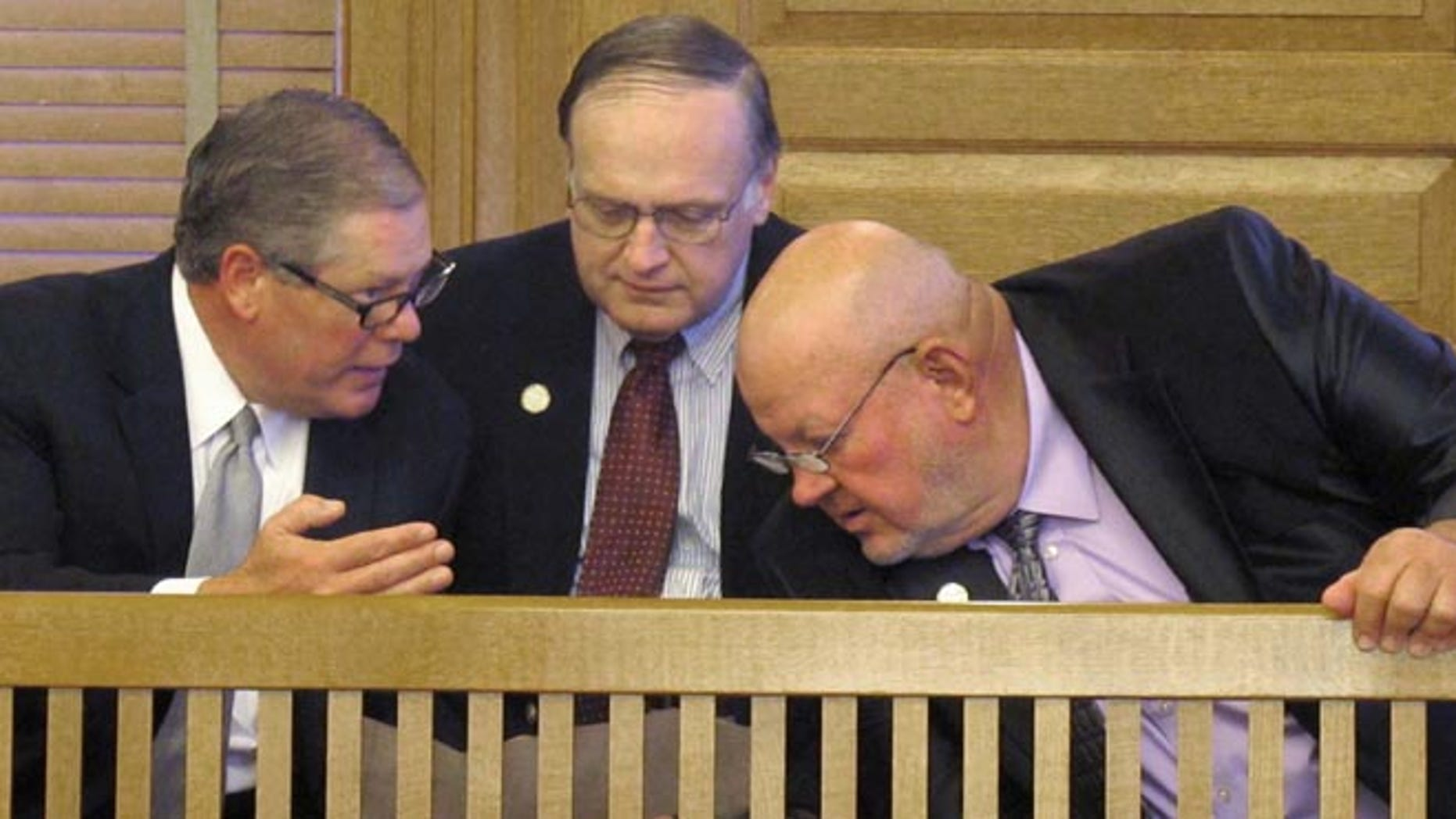 May 30, 2013: Jeff Freeman, left, a senior federal lobbyist for the National Rifle Association and former Kansas legislator, confers with Kansas state Reps. Ed Bideau, center, of Chanute, and Larry Hibbard, right, of Toronto, before a GOP caucus in the Statehouse in Topeka, Kan.
