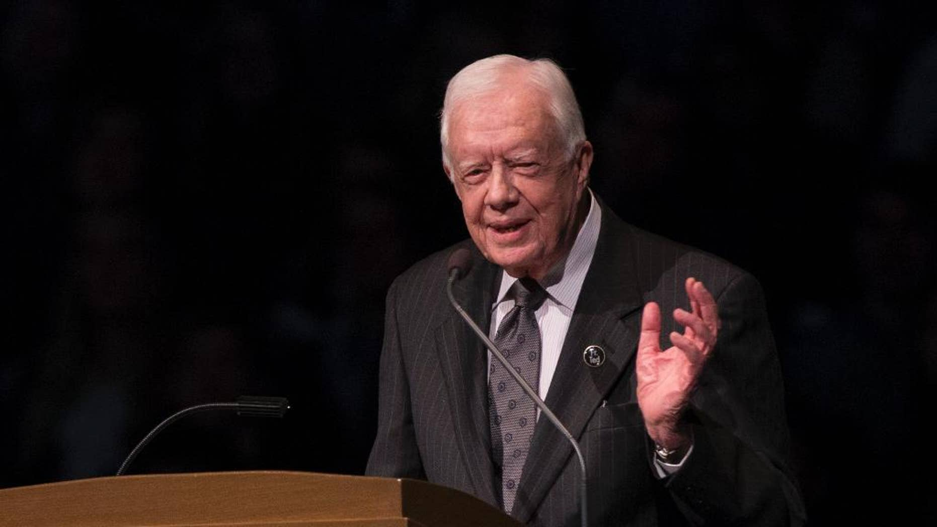 """FILE - In this March 4, 2015, file photo, former President Jimmy Carter speaks during the memorial service for Rev. Theodore Hesburgh, inside the Purcell Pavilion at the University of Notre Dame in South Bend, Ind. Carter Center officials said Sunday, May 10, 2015, that the former President has cut short an election observation visit in Guyana due to health reasons. The statement from the Center says the 90-year-old ex-president is returning to Atlanta. It did not disclose specifics, only saying Carter was """"not feeling well.""""(AP Photo/Robert Franklin, File)"""