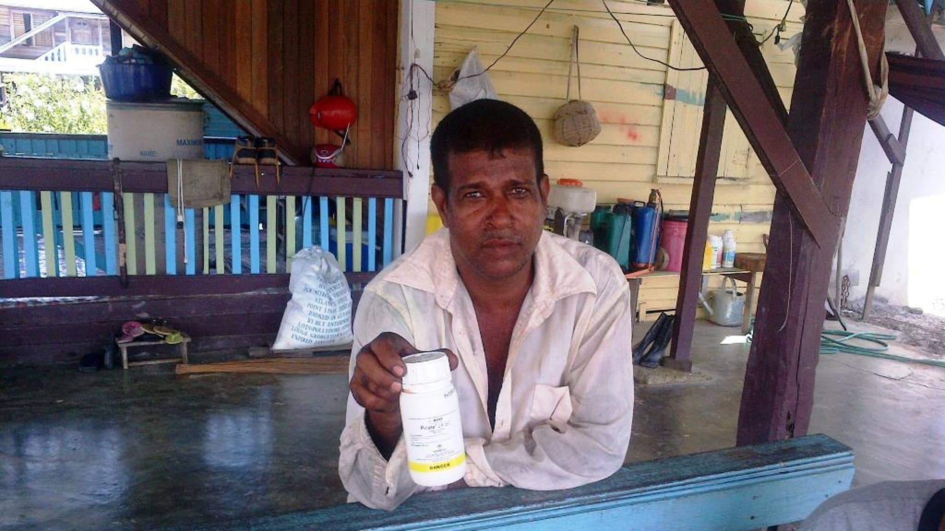 In this Monday, Oct. 6, 2014 photo, Vijai Ramlackhan holds a container of pesticide similar to the type his 17-year-old son used to commit suicide on their farm in the Berbice region of Guyana, a country that the World Health Organization says has the highest rate of suicide in the world. (AP Photo/Bert Wilkinson)