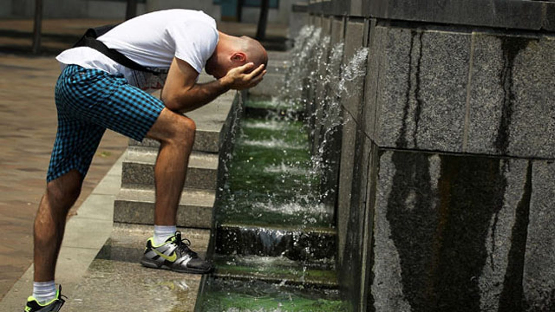 WASHINGTON, DC - JUNE 22:  Alexandar Zivkovic of Belgrade, Serbia, cools himself off at the fountain of the U.S. Navy Memorial June 22, 2012 in Washington, DC. Weather forecast predicted the area is heading towards a cooler weekend.  (Photo by Alex Wong/Getty Images)